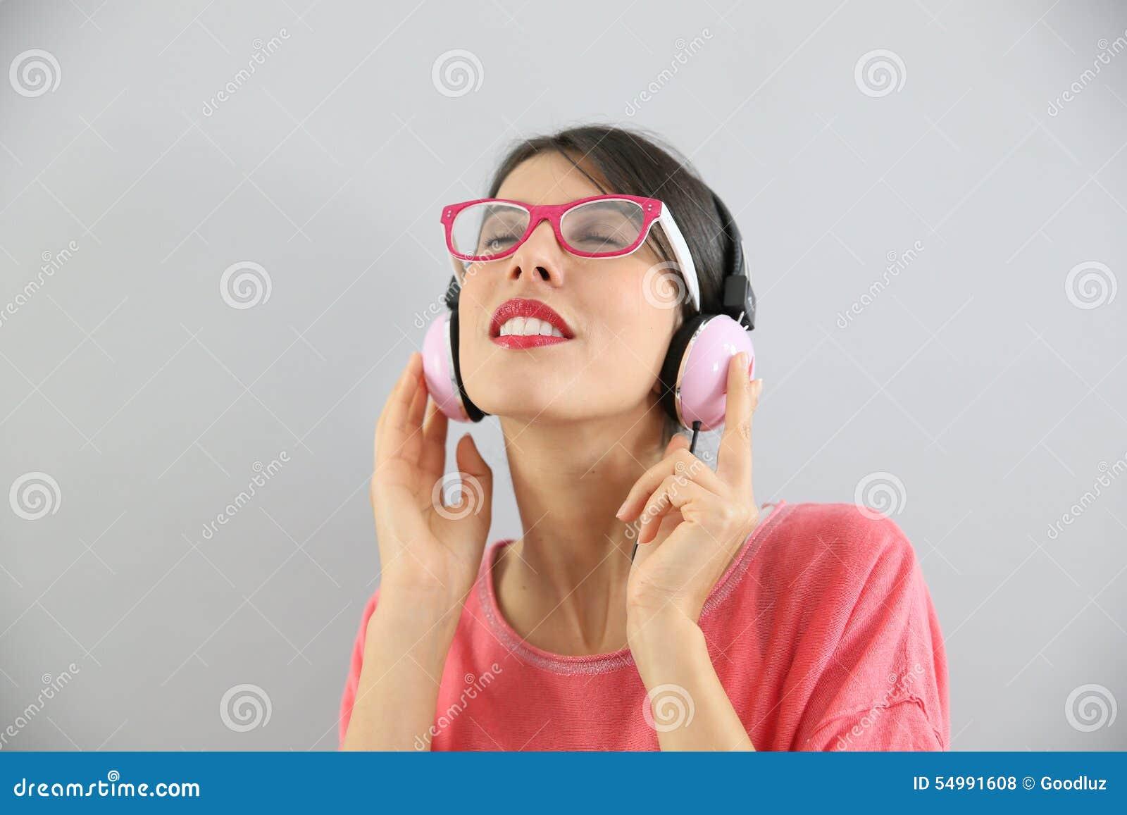Ung kvinna som lyssnar till musik och tycker om