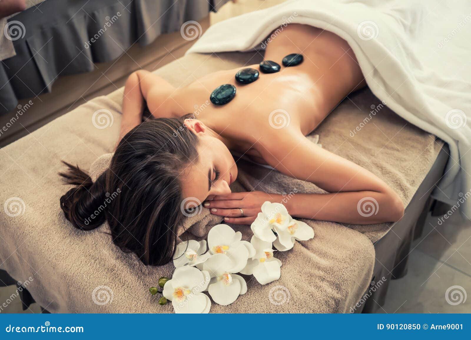 Ung kvinna som ner ligger med traditionella varma stenar längs spien