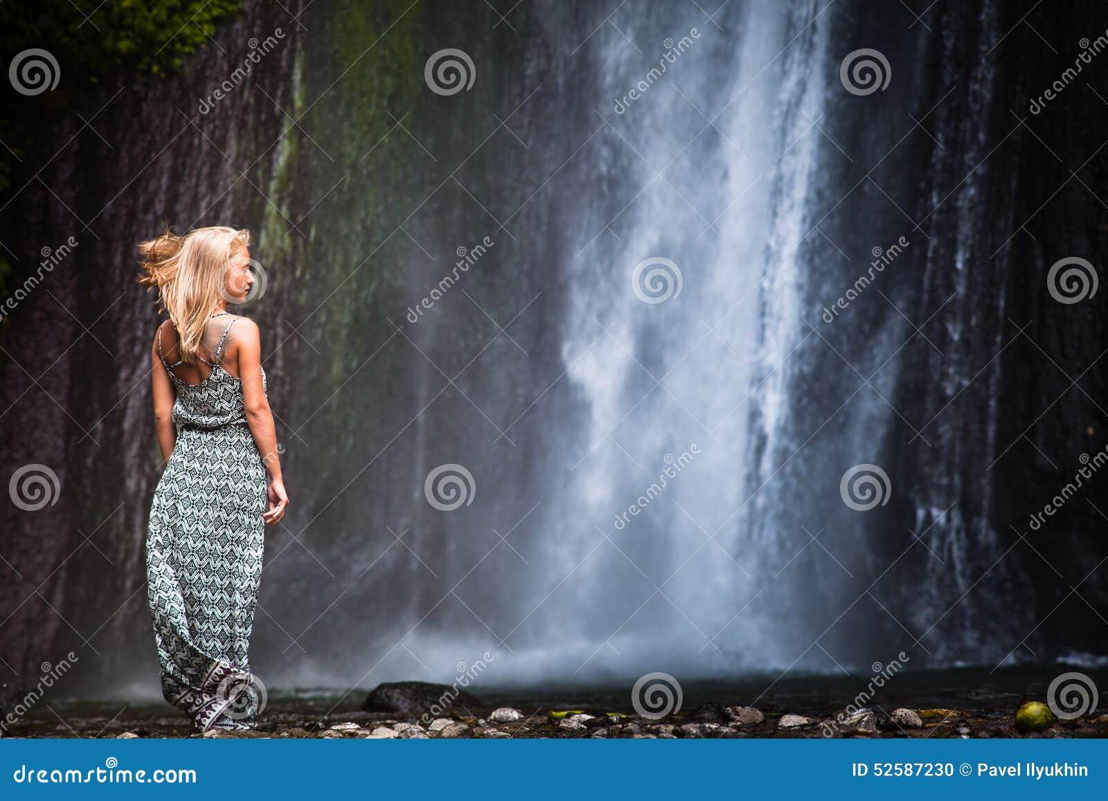 Ung kvinna som reser till vattenfallet