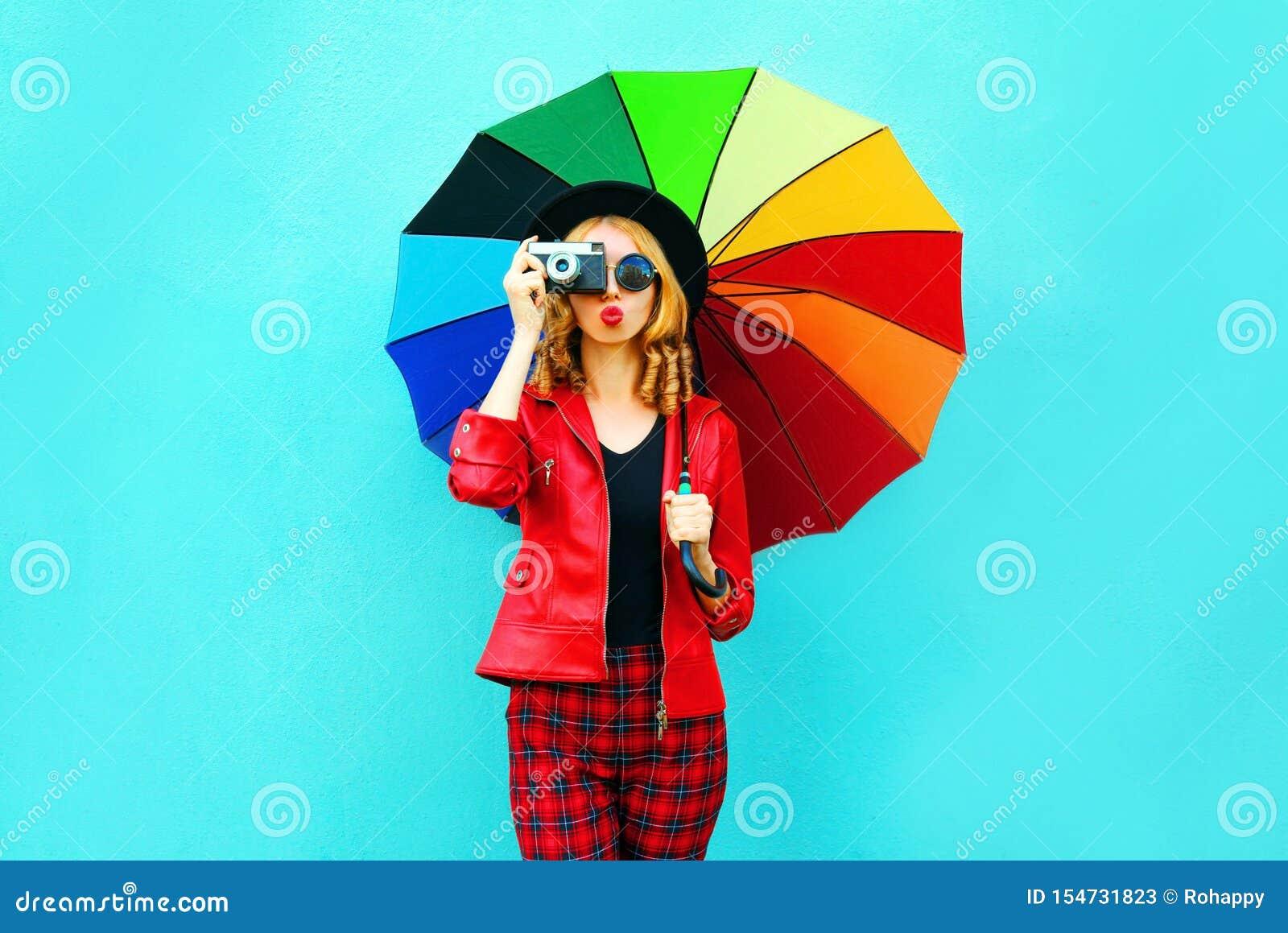 Ung kvinna som rymmer det färgrika paraplyet, retro kamera som tar bilden i det röda omslaget, svart hatt på den blåa väggen