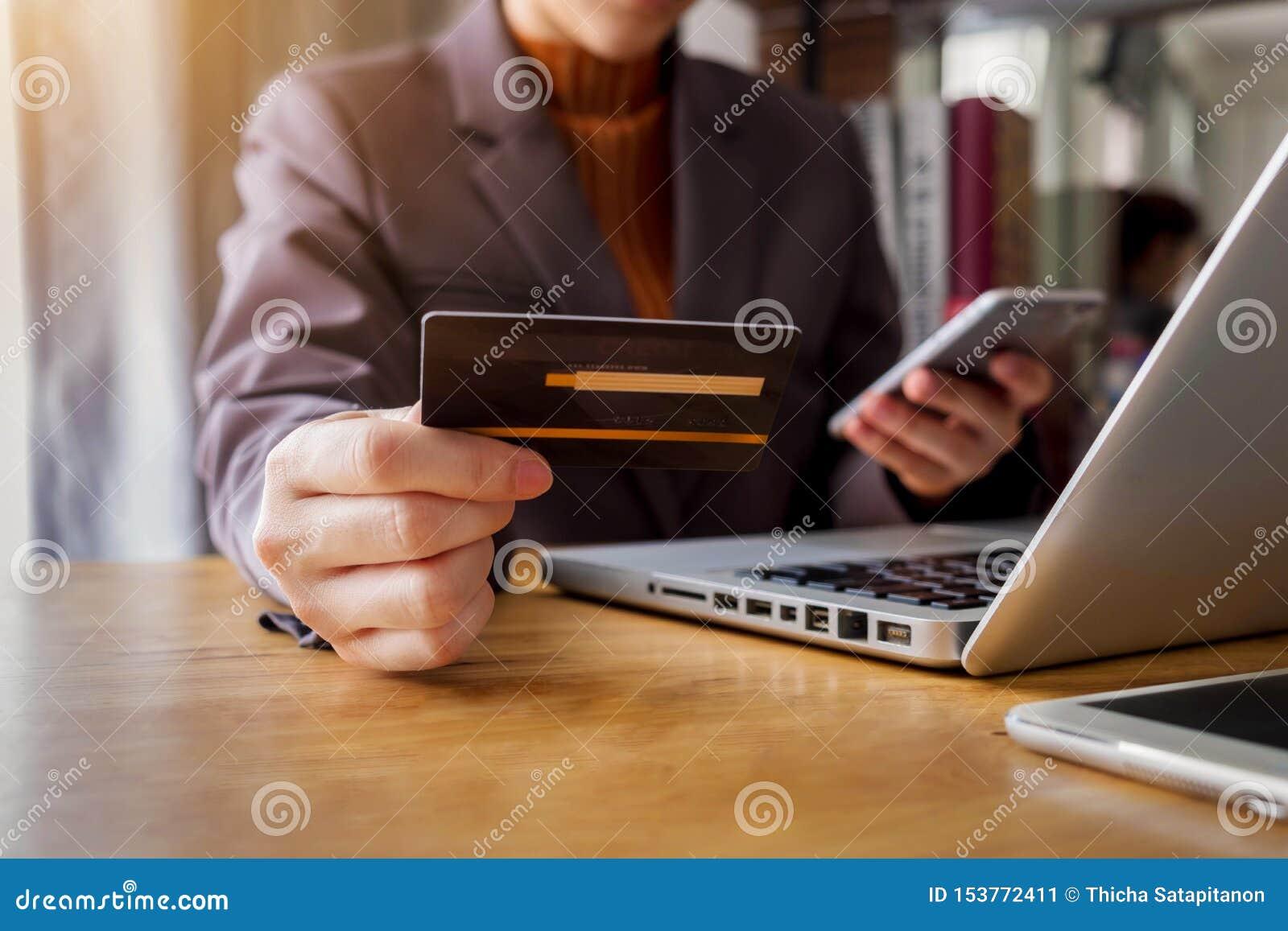 Ung kvinna som rymmer en kreditkort för att inhandla on-line shopping