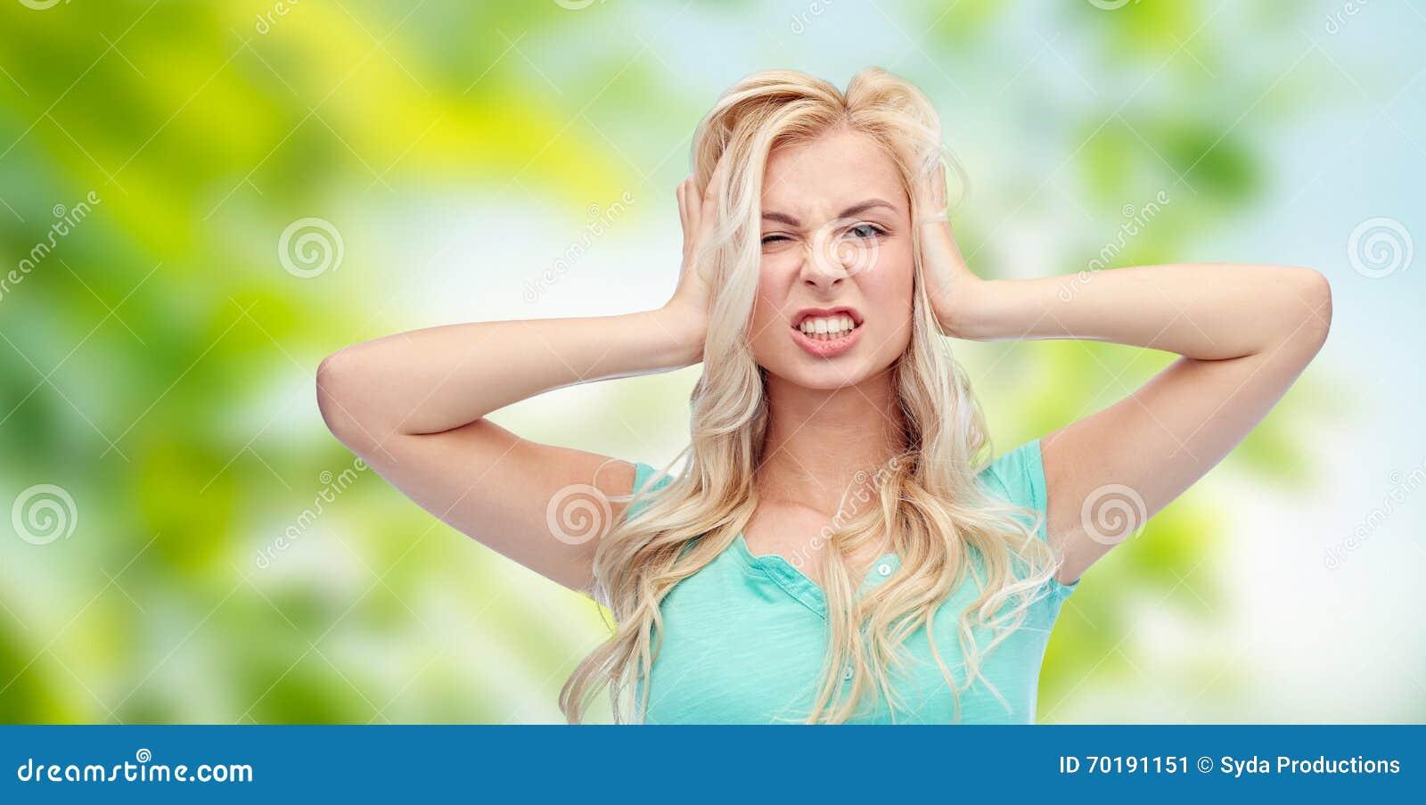 Ung kvinna som rymmer till hennes huvud och skrika