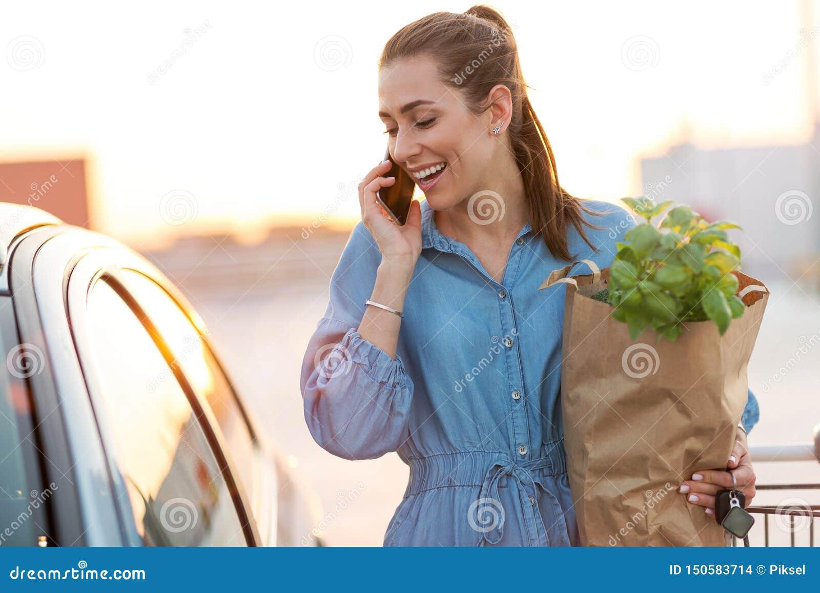 Ung kvinna som sätter livsmedel på bilstammen