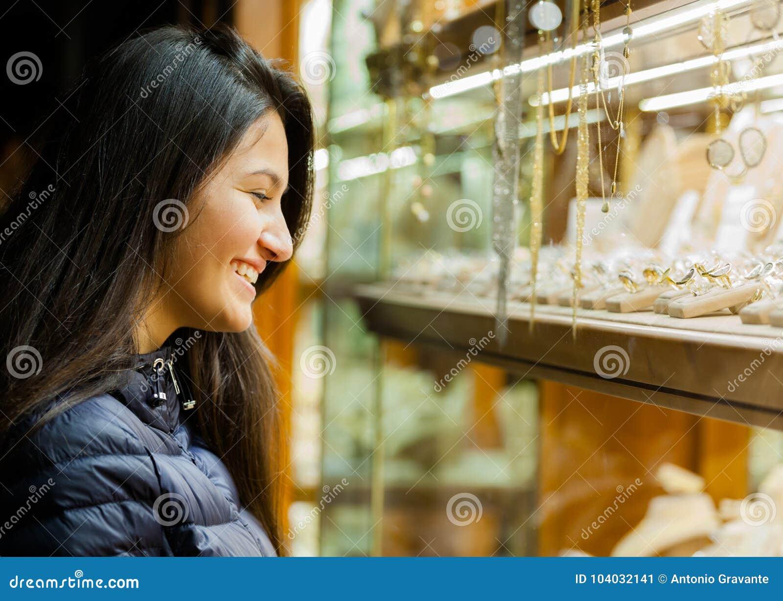 Ung kvinna som ser ställa ut av utomhus- smycken