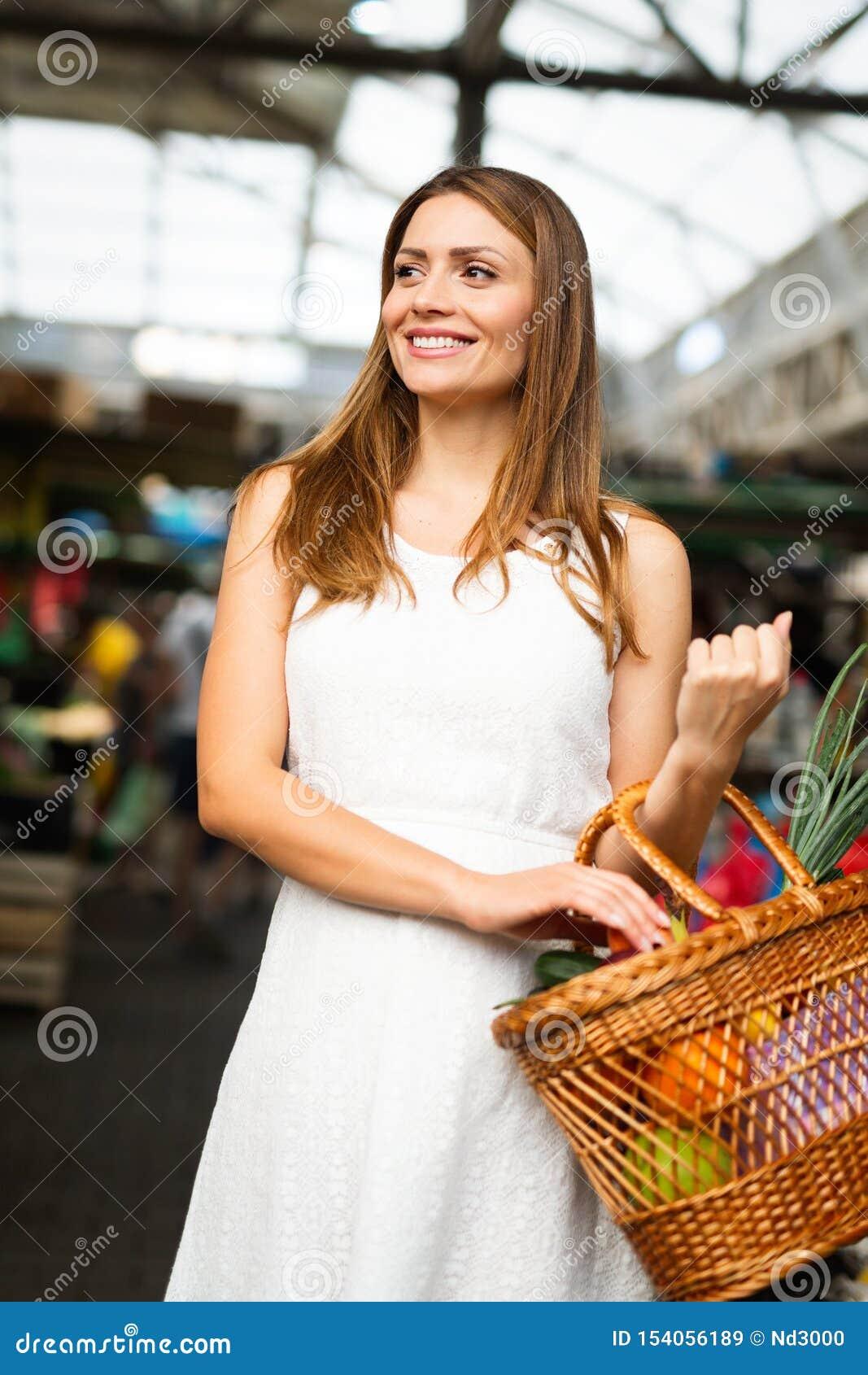 Ung kvinna som shoppar sund mat på marknaden