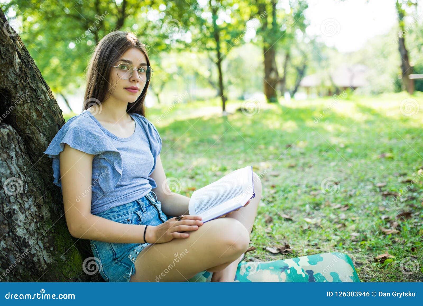 Ung kvinna som sitter och läser hennes favorit- bok på gröna gras för nolla under träd i en trevlig solig sommar