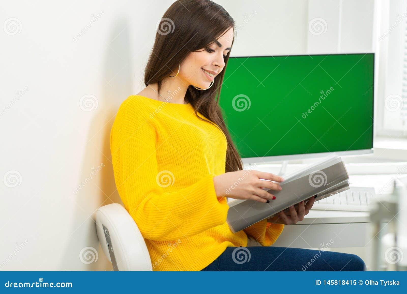 Ung kvinna som sitter på arbetsplatsen och i regeringsställning läser papper På bakgrunden är en grön skärm