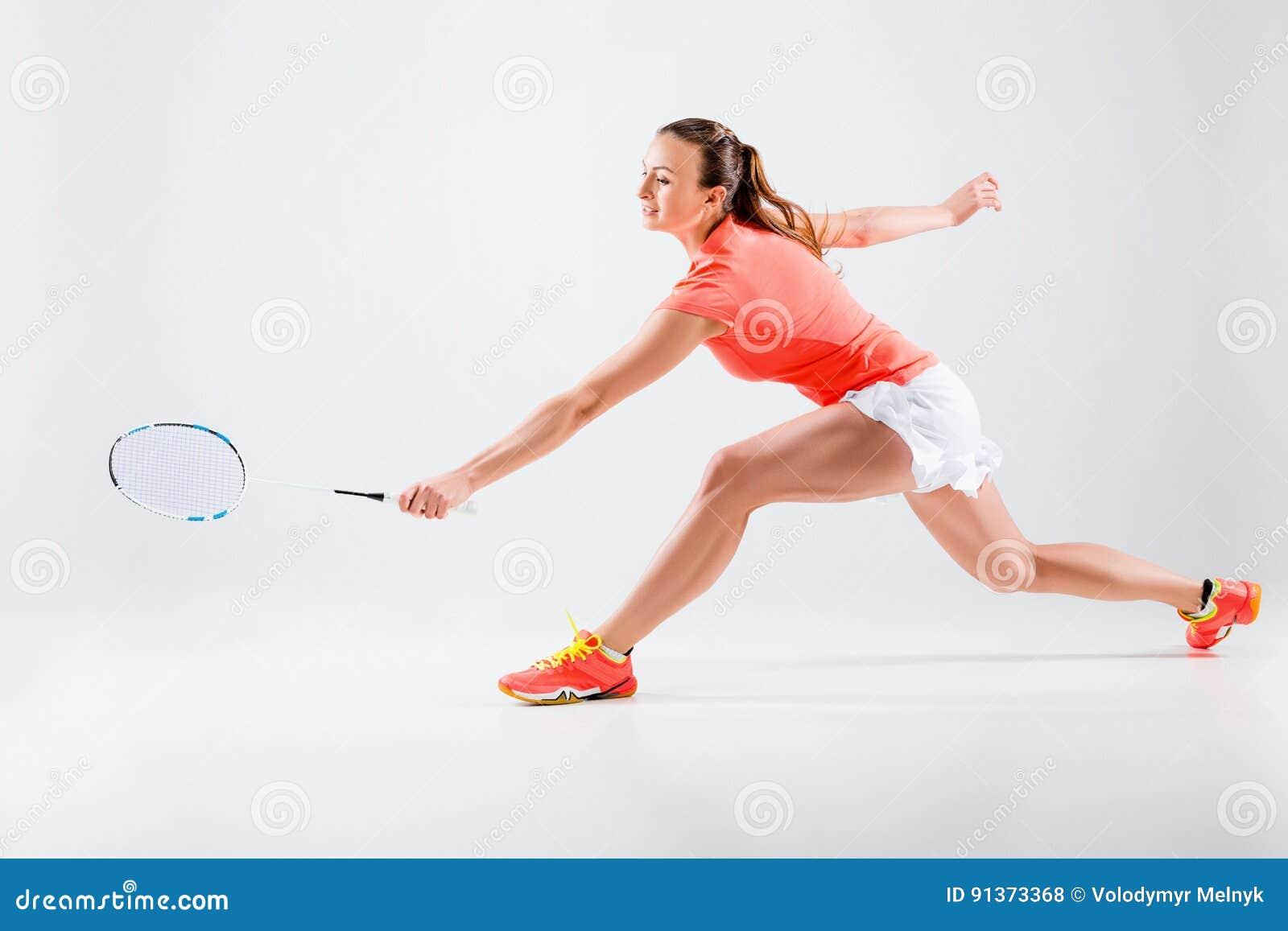 Ung kvinna som spelar badminton över vit bakgrund