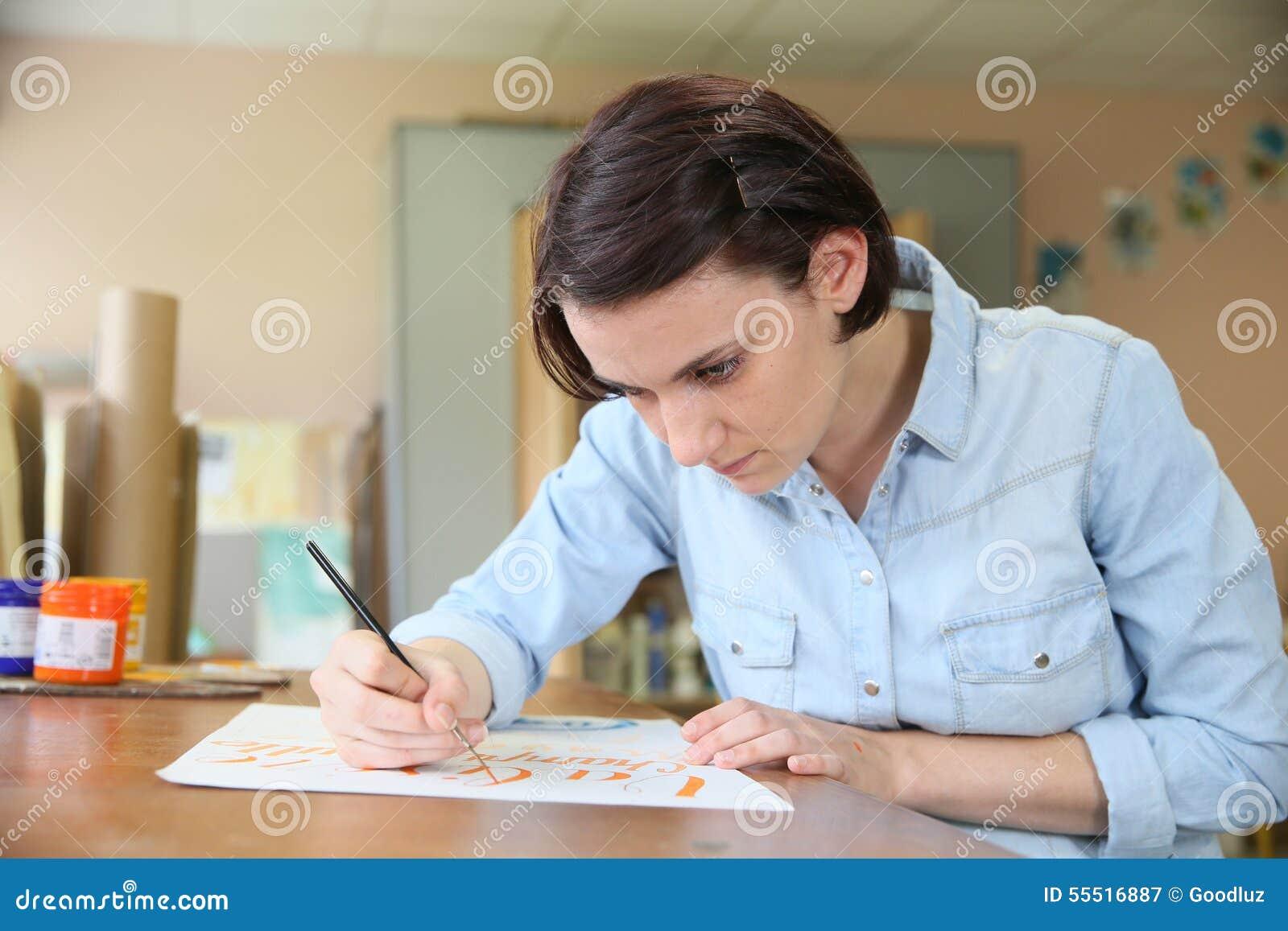 Ung kvinna som studerar dekorativ målning