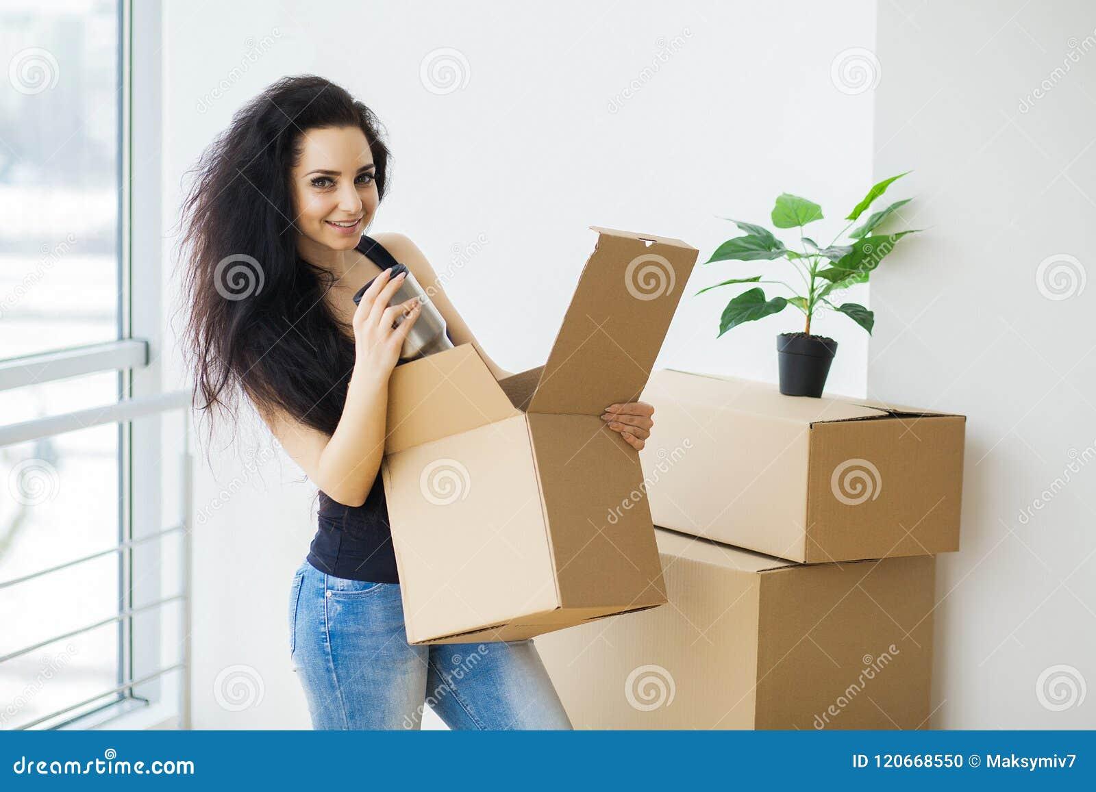 Ung kvinna som tappar kartongen home flytta sig som är nytt