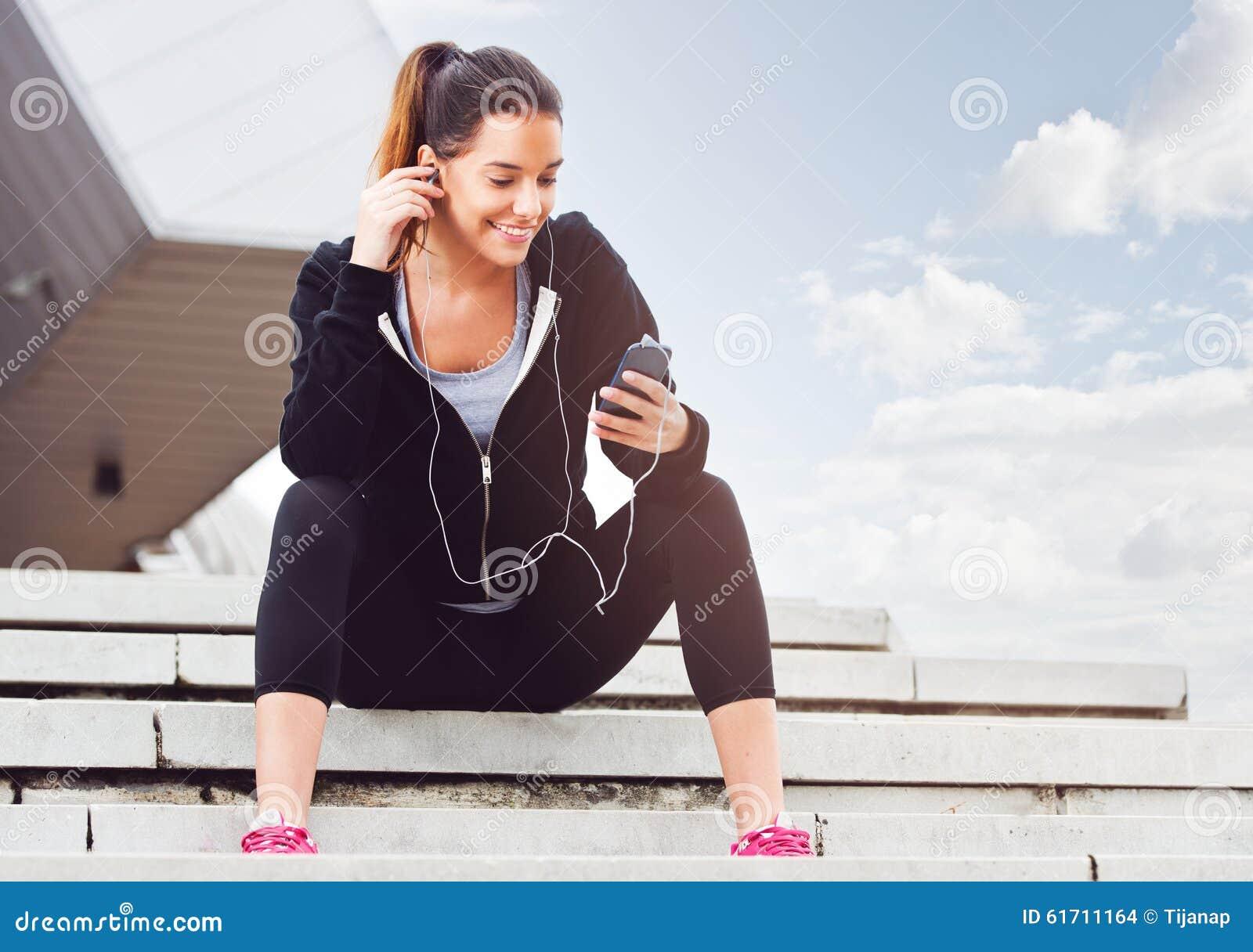 Ung kvinna som tar ett avbrott från att öva utanför med mobiltelefonen