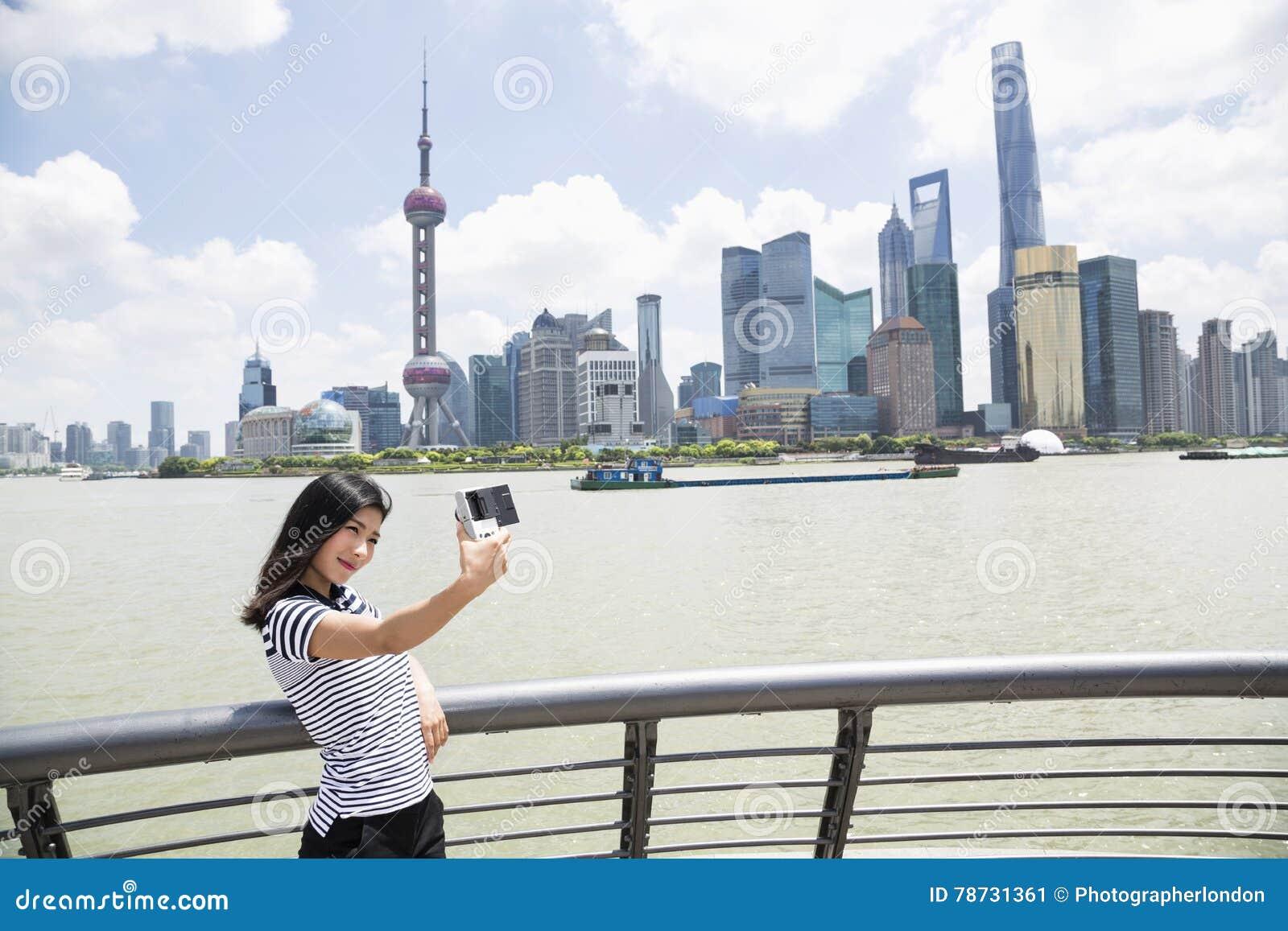 Ung kvinna som tar selfie, medan stå vid räcket mot Pudong horisont