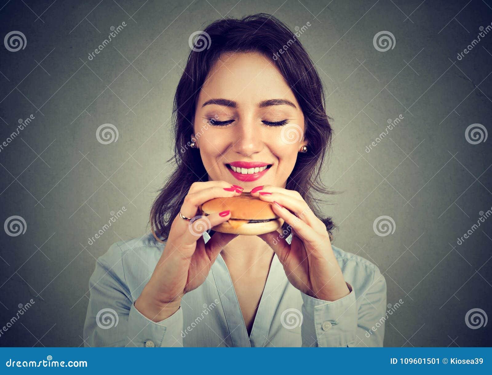 Ung kvinna som tycker om snabbmat