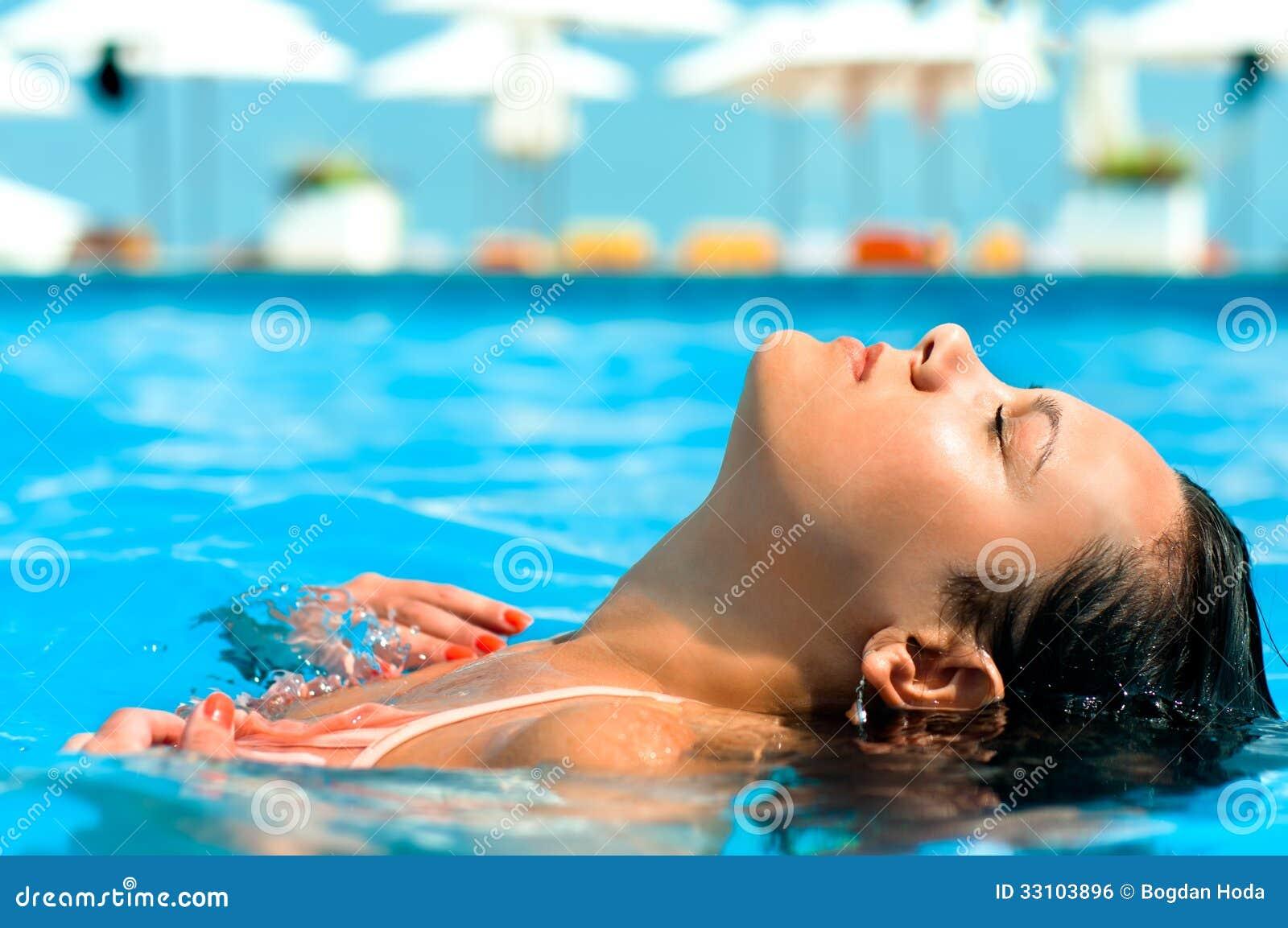 Ung kvinna som tycker om vatten och solen i utomhus- simbassäng