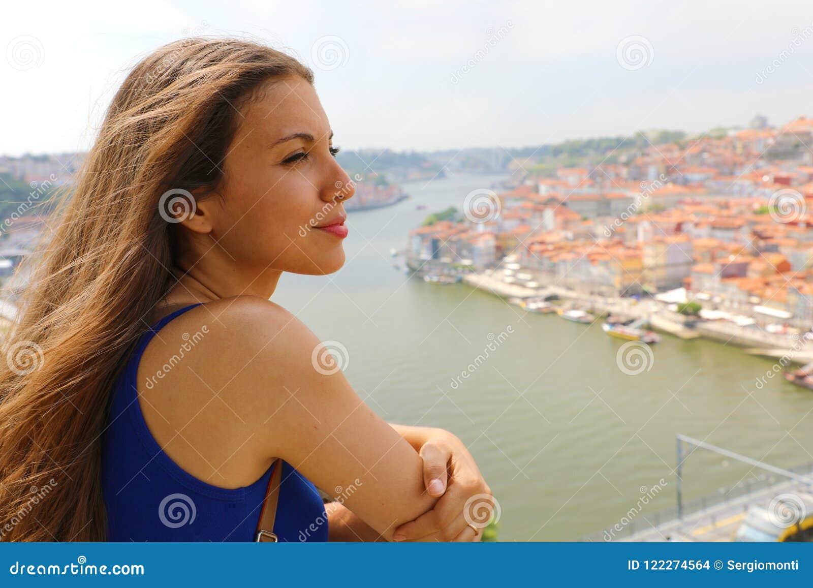 Ung kvinna som tycker om vind i hennes framsida, när se den Porto staden, Portugal, Europa