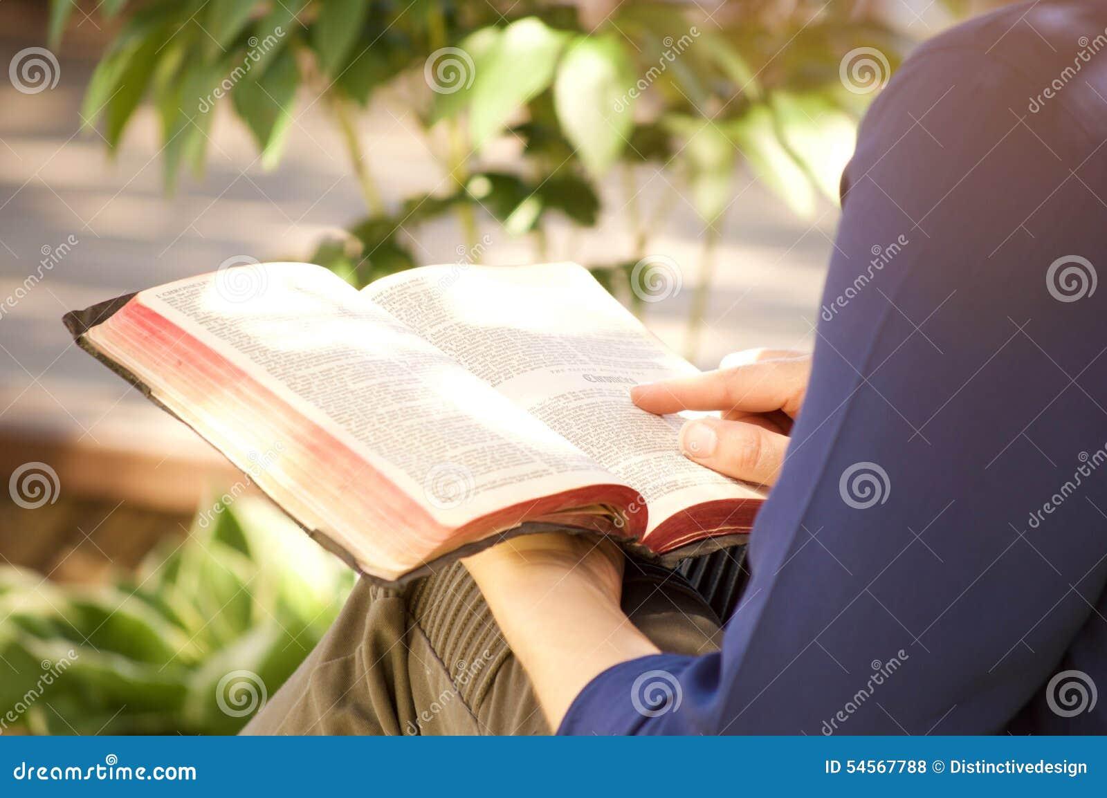 Ung kvinna som utanför läser den heliga bibeln