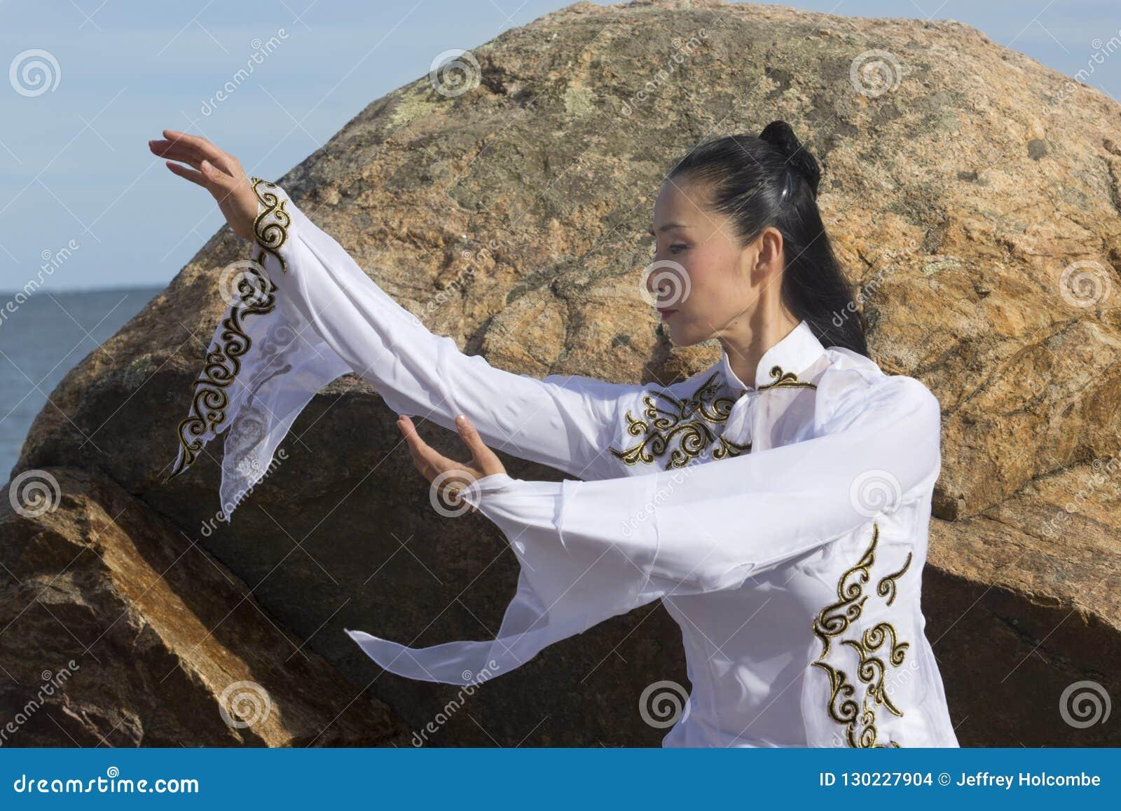 Ung kvinna som utför den qi gongen på en stenig Connecticut strand