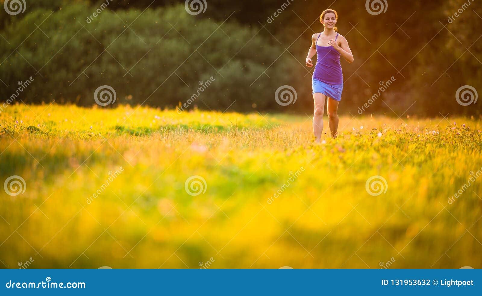 Ung kvinna som utomhus kör på älskvärda soliga evenis för en sommar