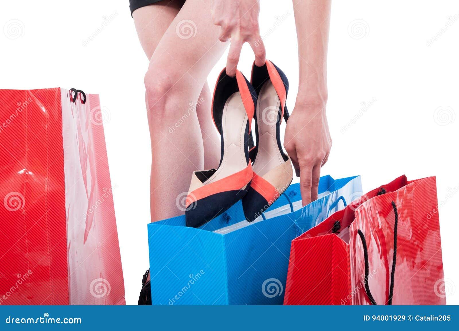 Ung kvinna som väljer skor i ett skolager