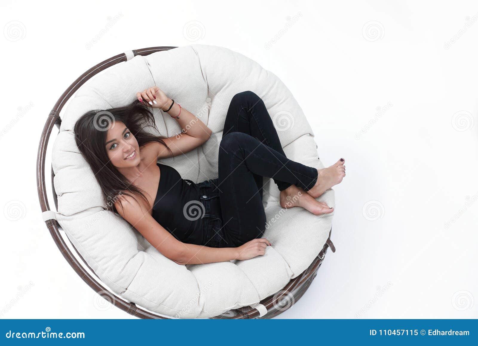 Ung kvinna som vilar i stor bekväm fåtölj