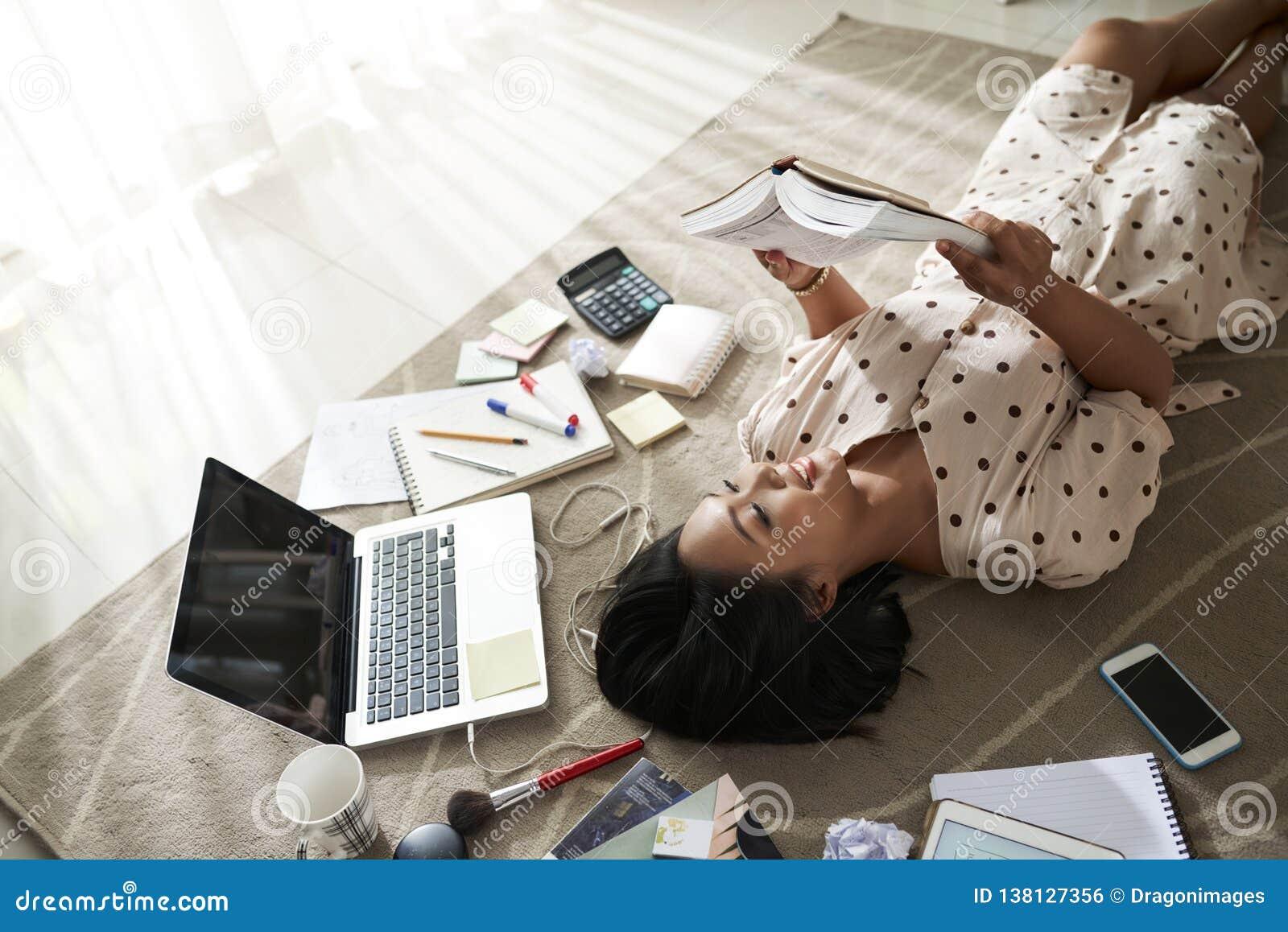 Ung kvinna som vilar med boken
