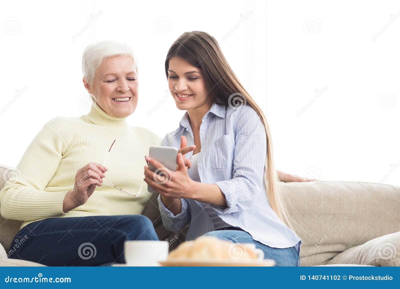Ung kvinna som visar foto till modern, genom att använda smartphonen