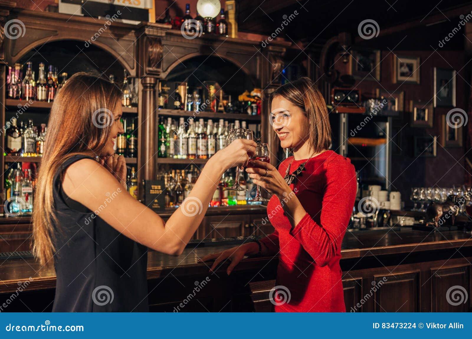Ung kvinna två nära en stång som dricker och pratar varje andra