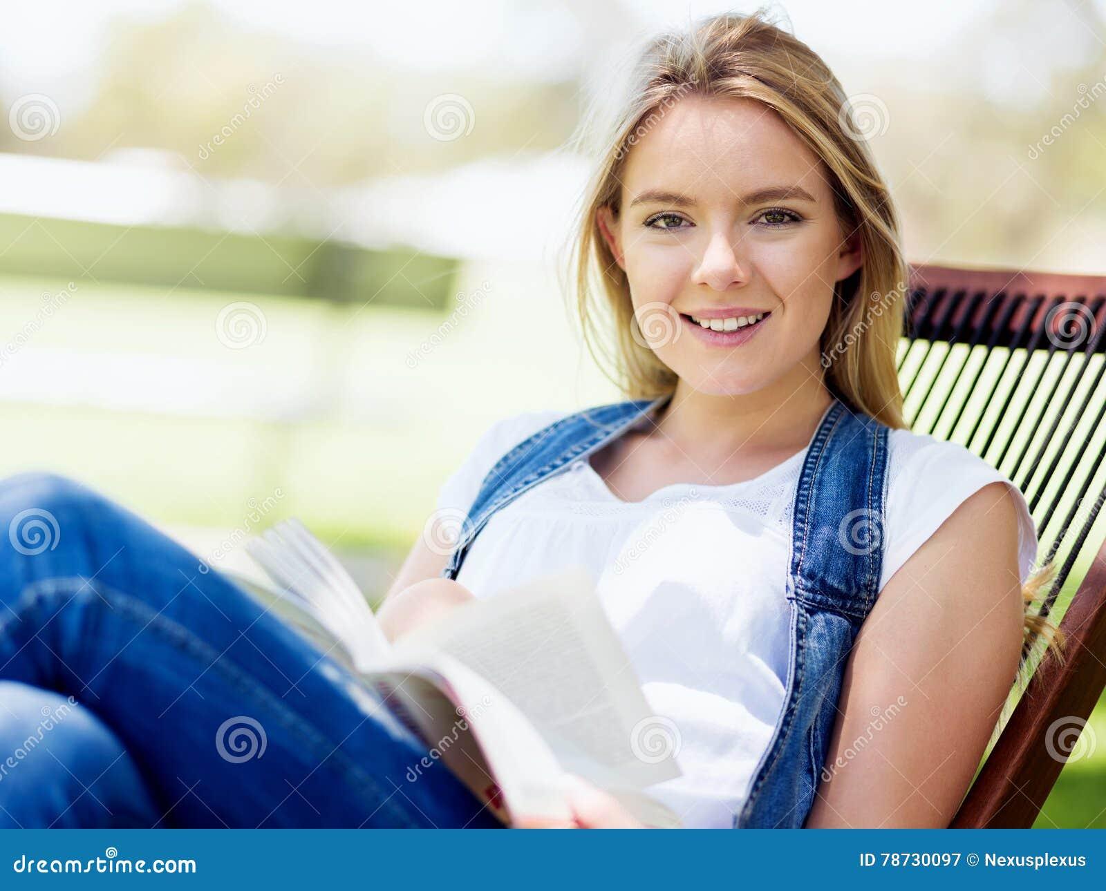 Ung kvinnaläsning som en boka parkerar in