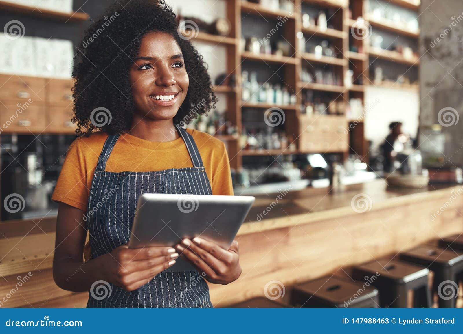 Ung kvinnlig ägare som rymmer den digitala minnestavlan i hennes kafé som ser aw