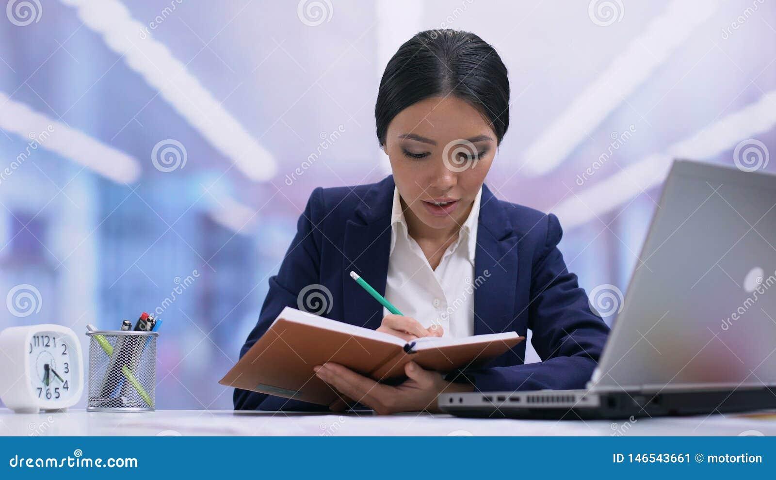 Ung kvinnlig anställd som skriver i anteckningsboken som planerar arbetsdag, idéer, disciplin arkivfilmer