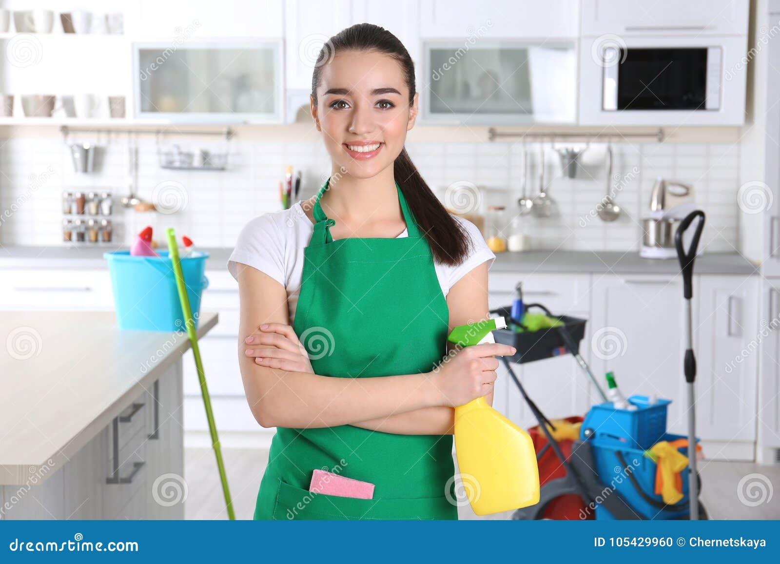 Ung kvinnlig arbetare med flaskan av tvättmedel