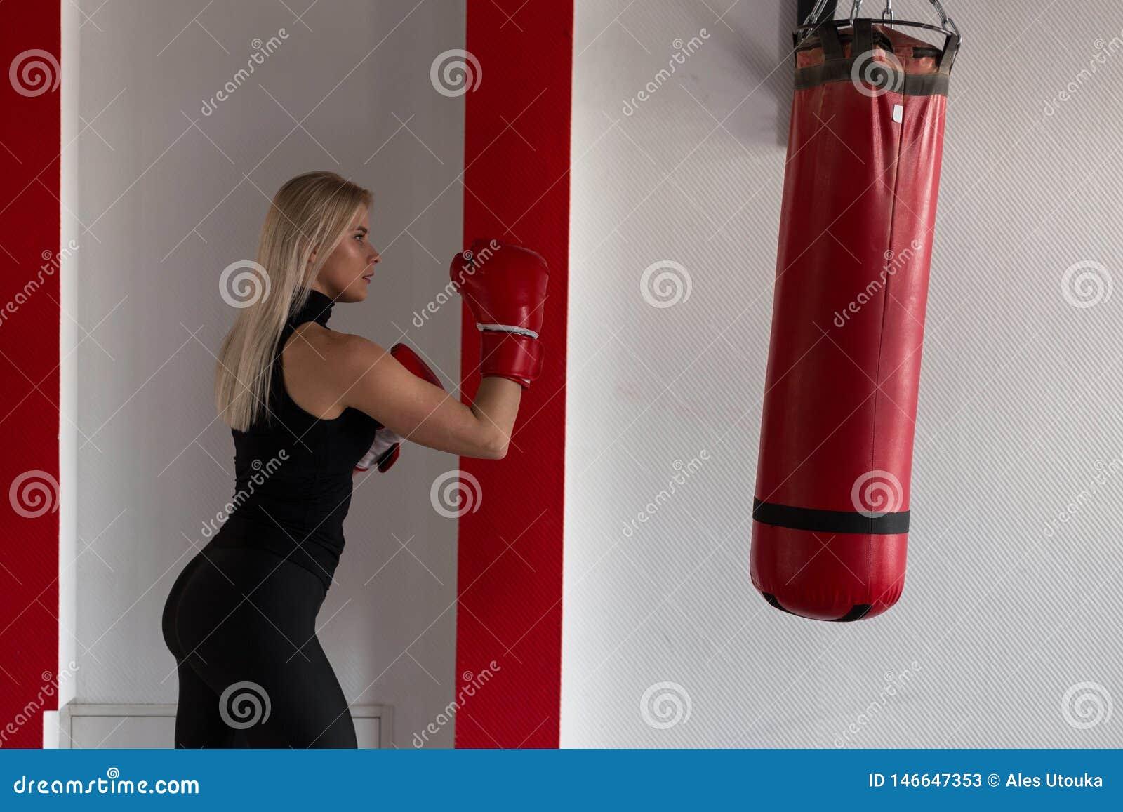 Ung kvinnlig boxare i röda boxas handskar i rörelse som slår en stansa påse Flickan utbildar i idrottshallen Boxningbegrepp