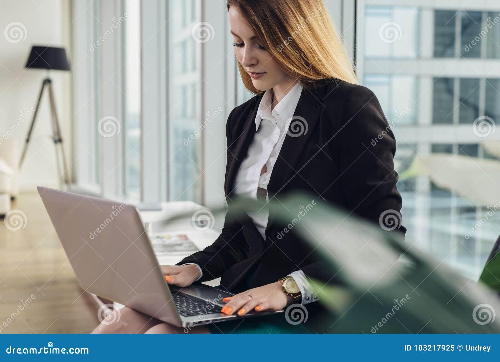 Ung kvinnlig copywriter som skriver en advertizingtextmaskinskrivning på bärbar datortangentbordet som i regeringsställning sitte