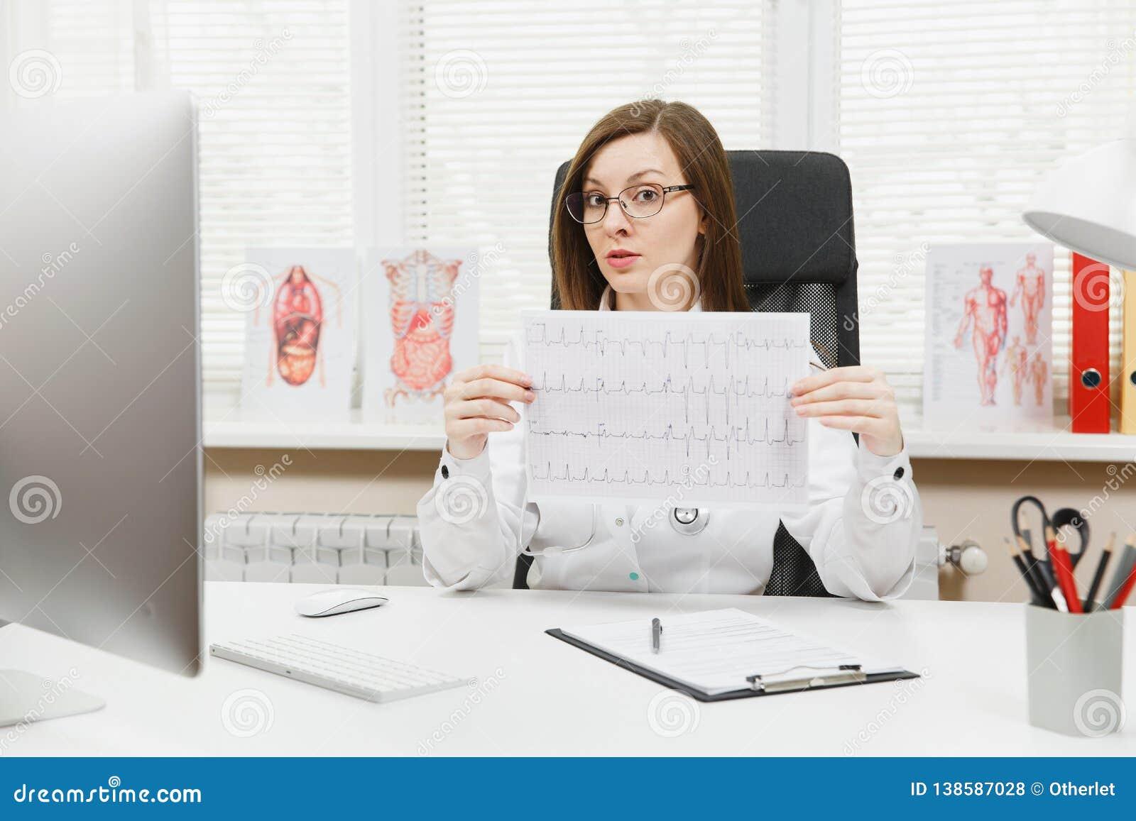 Ung kvinnlig doktor som sitter på skrivbordet med medicinska dokument, elektrokardiogramrekord, diagram för hjärtaekgkardiogram a