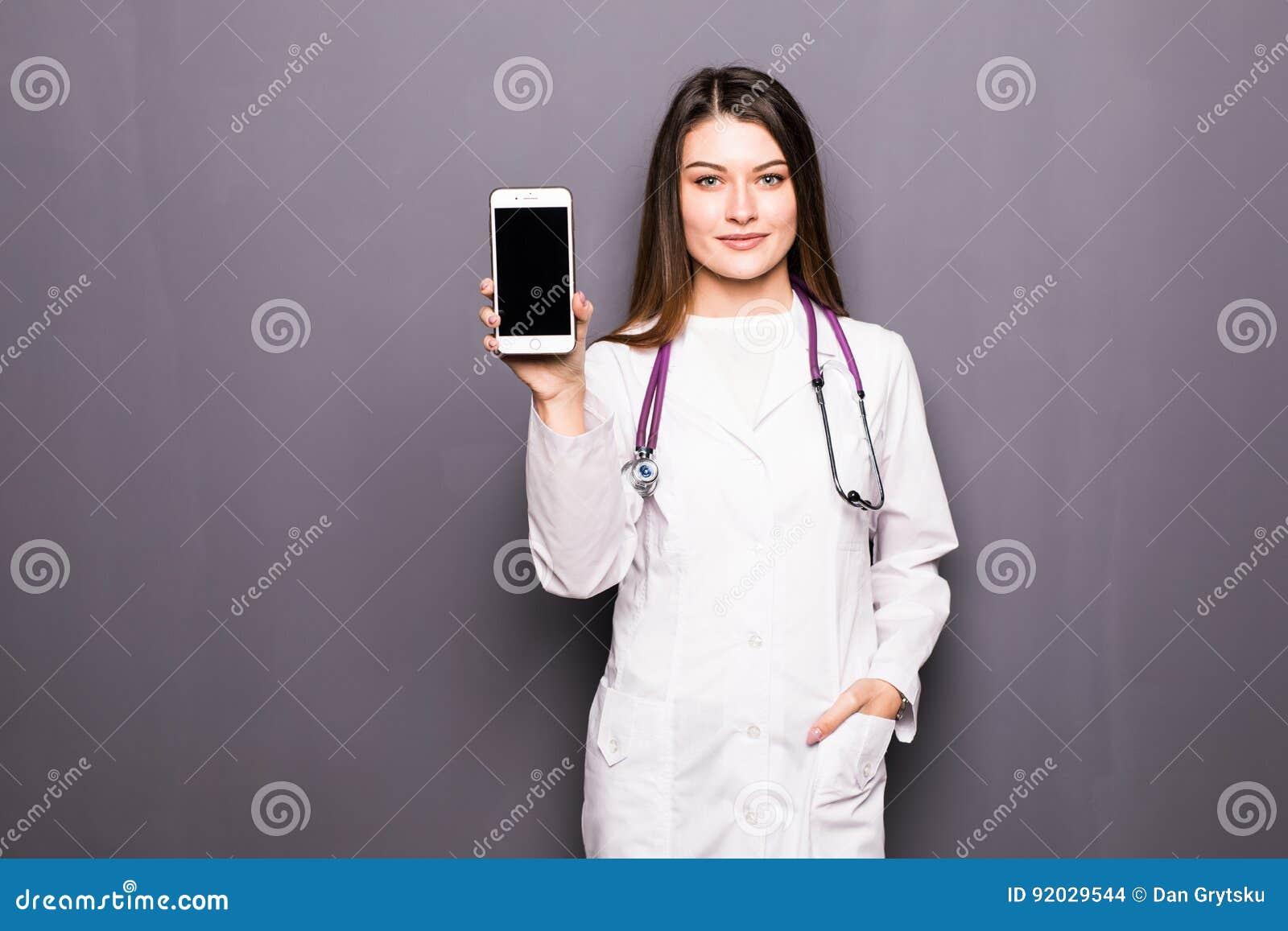 Ung kvinnlig doktorsvisningmobiltelefon mot grå bakgrund