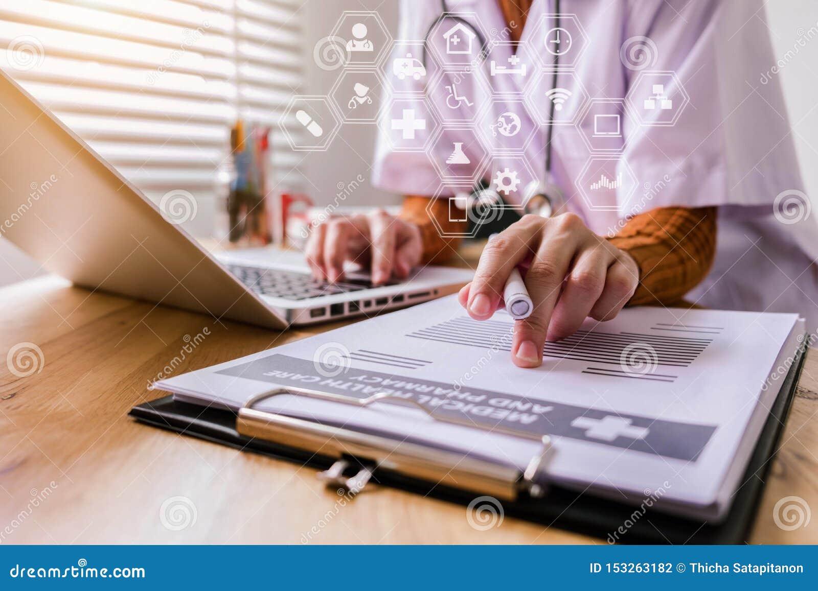 Ung kvinnlig i likformig av doktorn som använder bärbara datorn för digital teknologi för efterbehandlingsapparat och skriver en
