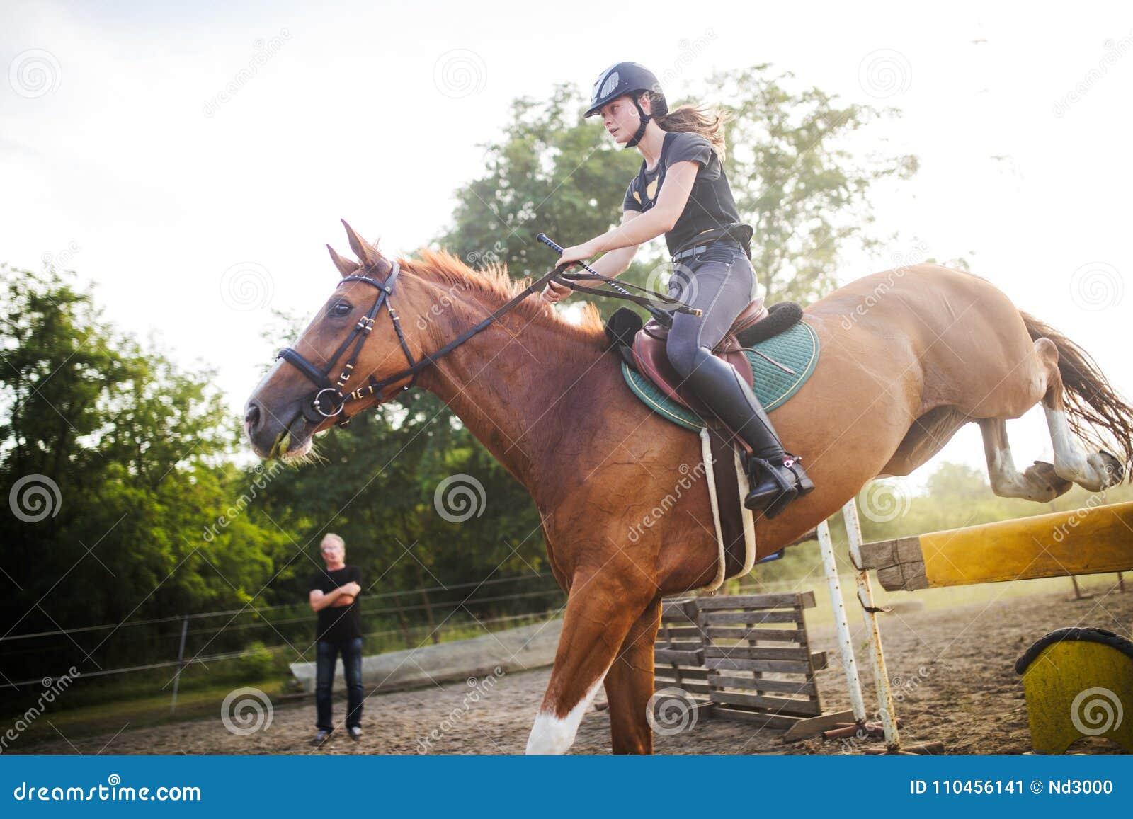 Ung kvinnlig jockey på hästen som hoppar över häck