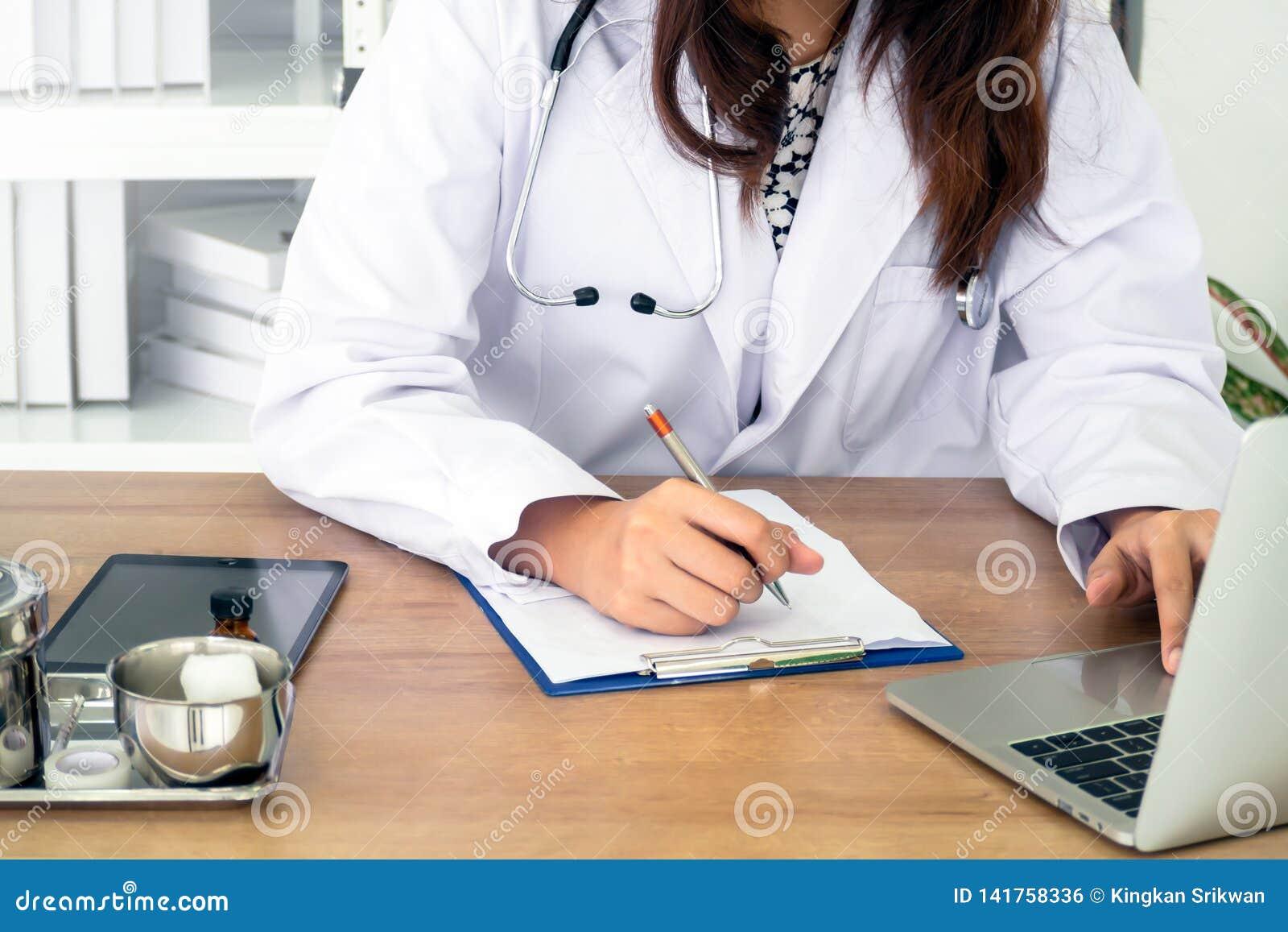 Ung kvinnlig läkare som använder bärbara datorn