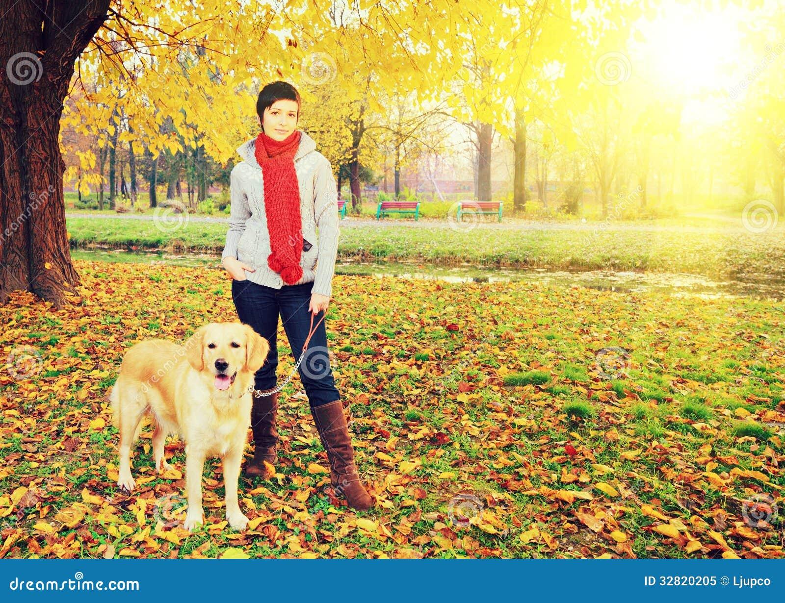 Ung kvinnlig och hennes hund som poserar i höst i en parkera på ett soligt D