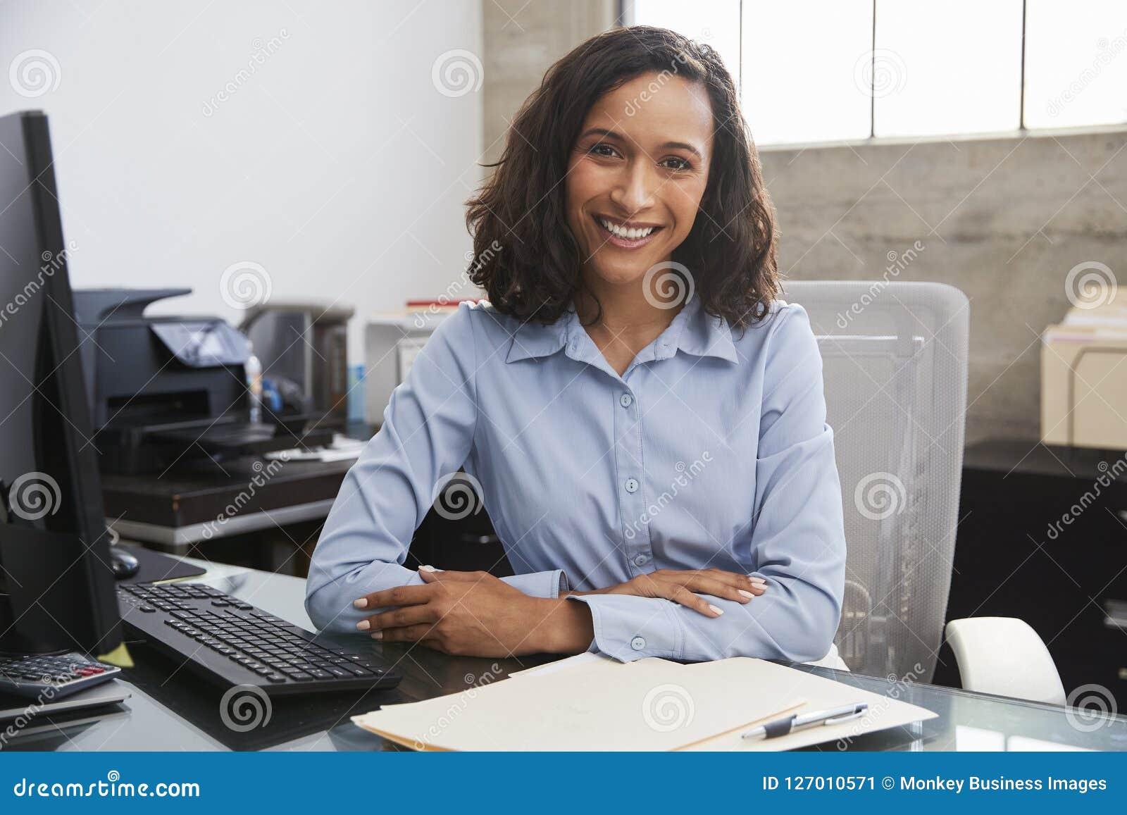 Ung kvinnlig professionell på skrivbordet som ler till kameran