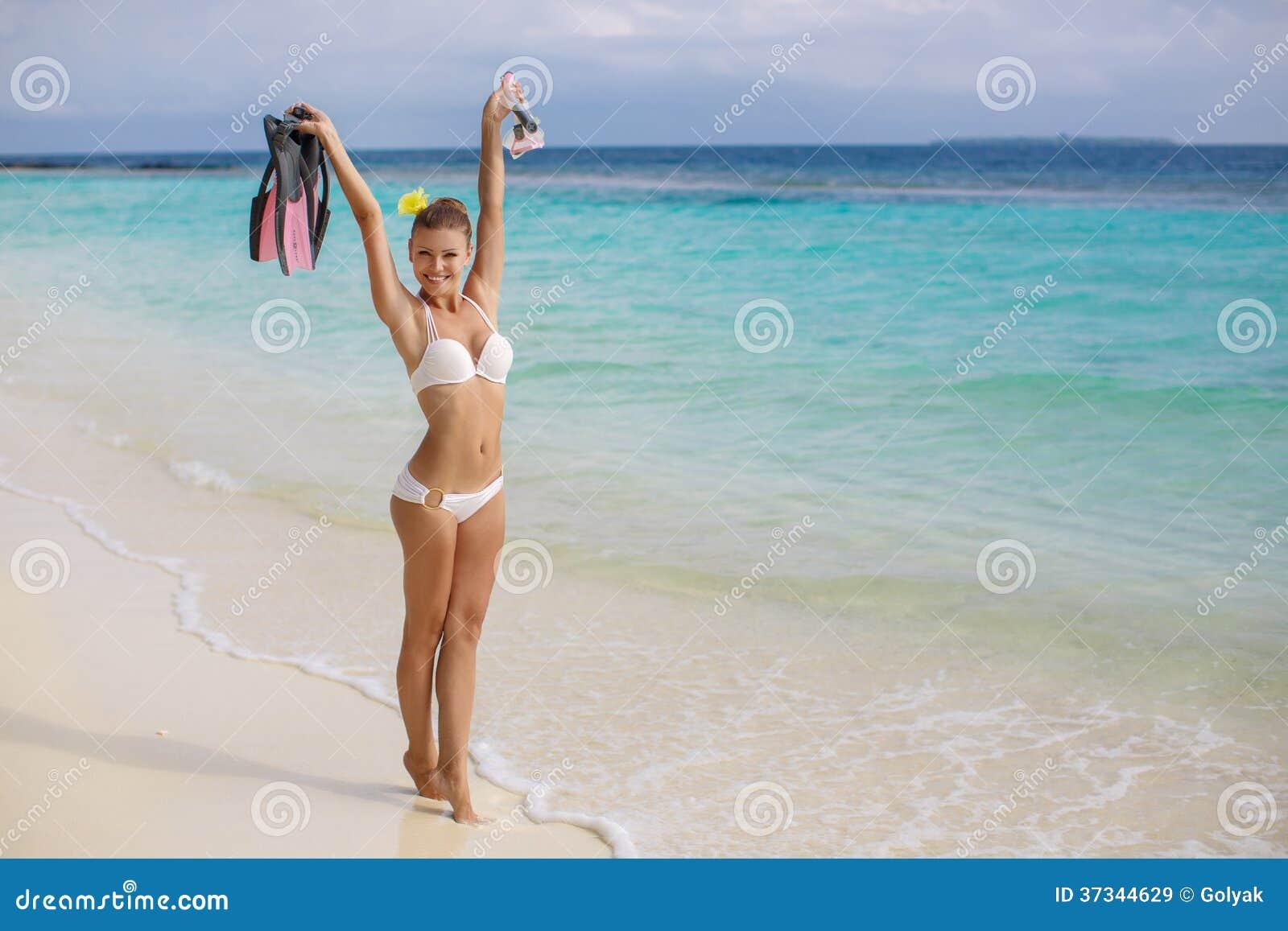 Ung kvinnlig som tycker om solig dag på den tropiska stranden