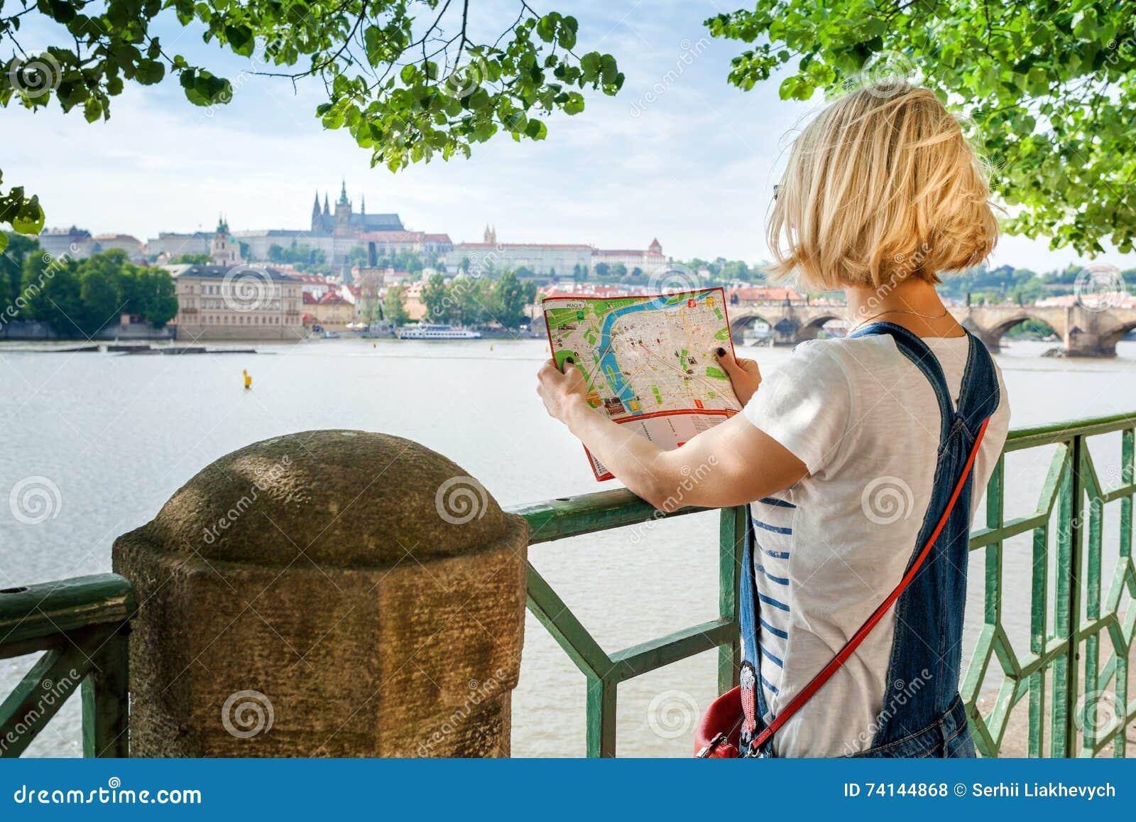 Ung kvinnlig turist som studerar en översikt av Prague