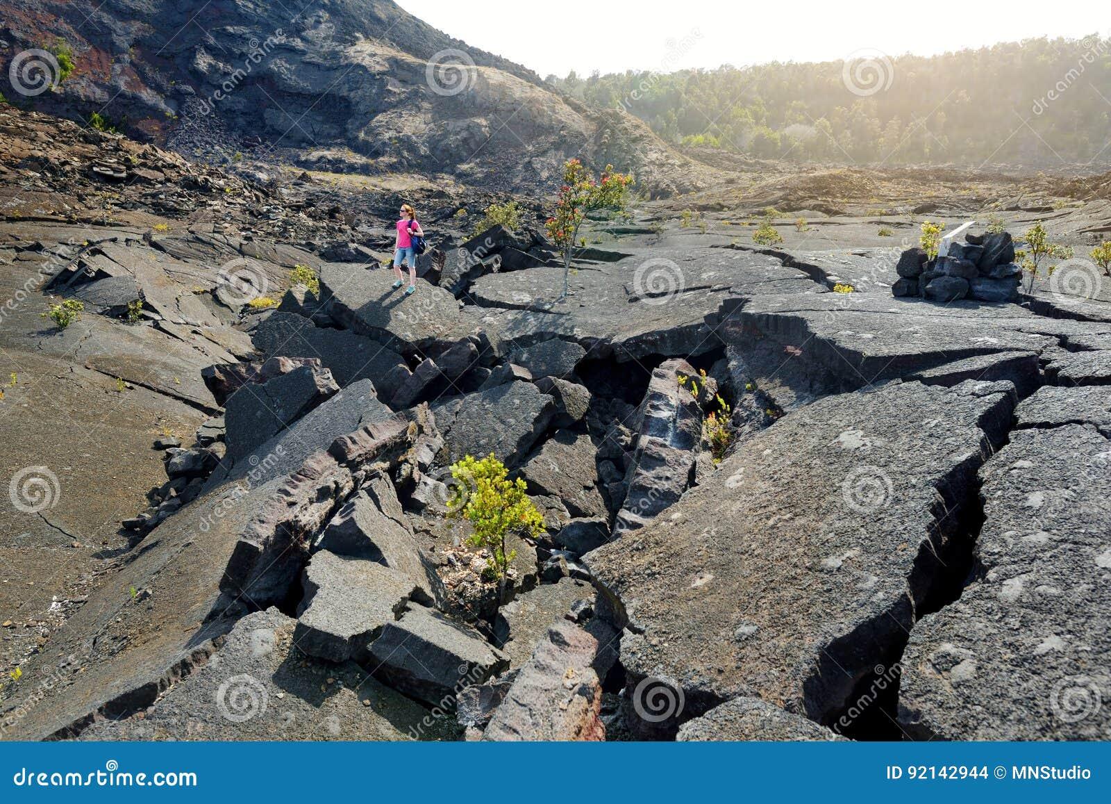 Ung kvinnlig turist- undersökande yttersida av den Kilauea Iki vulkankrater med att smula lava vaggar i Volcanoesnationalpark i B