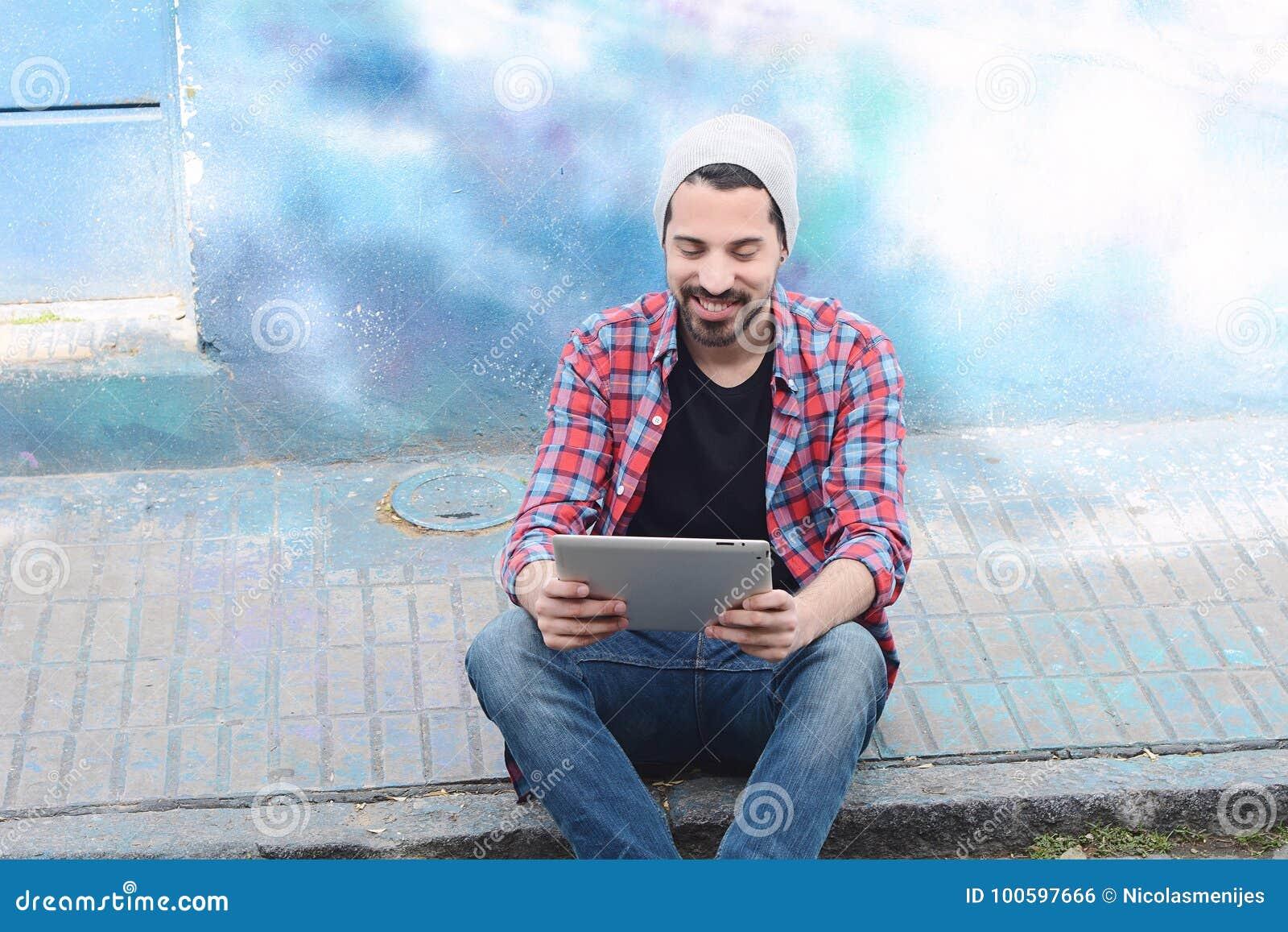 Ung latinsk man som använder en minnestavla