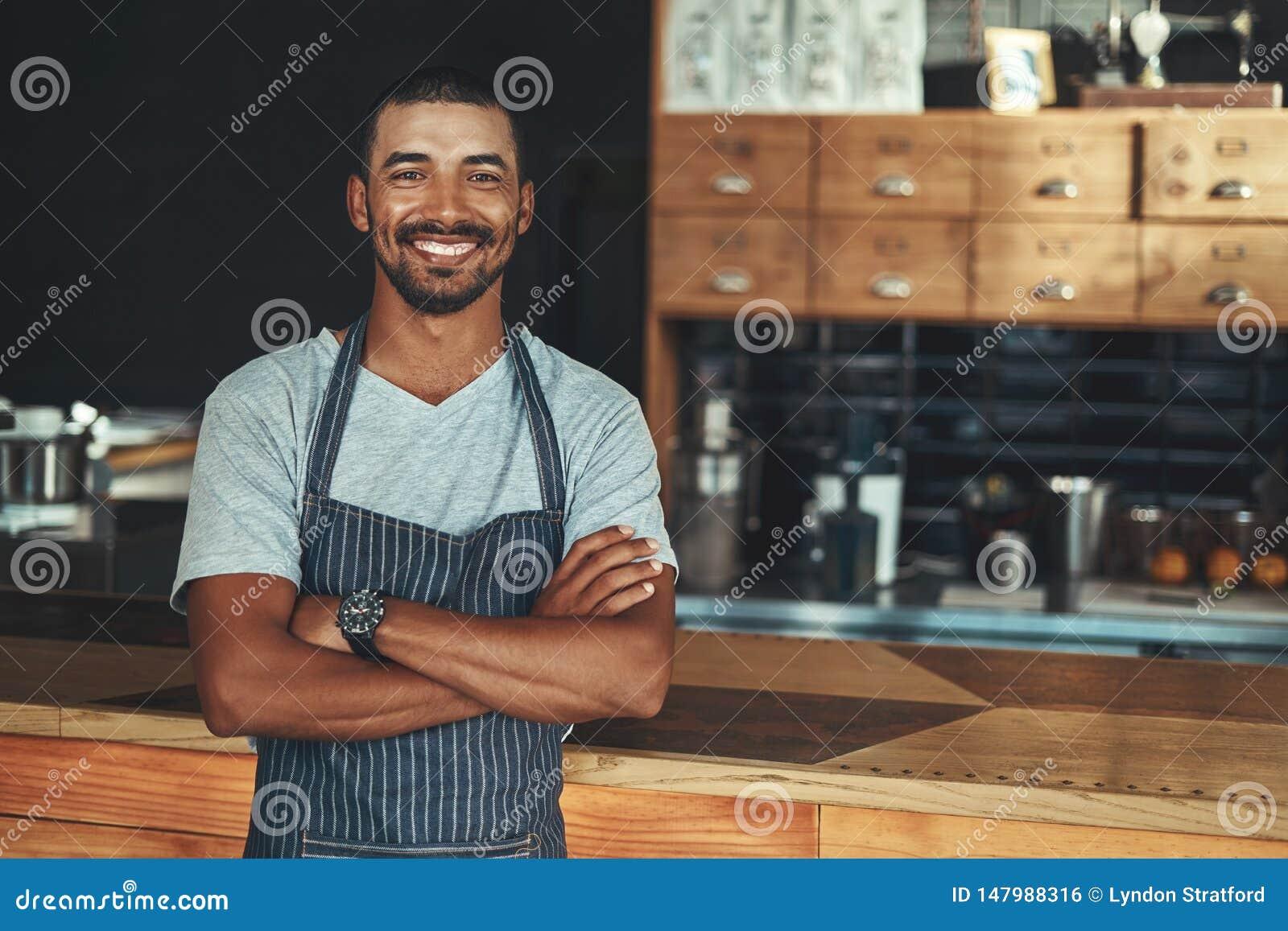 Ung le barista som poserar nära räknaren på hans kafé