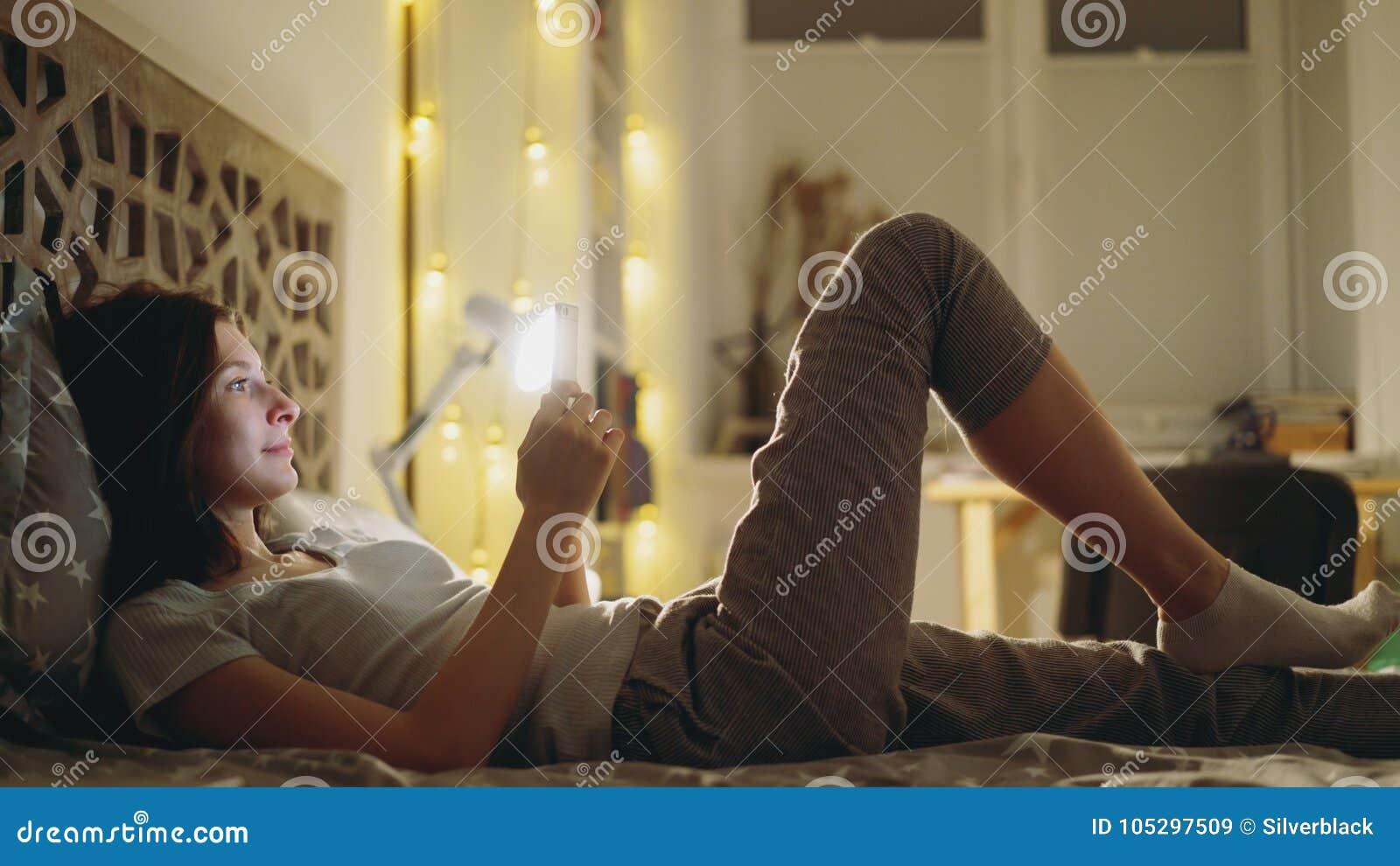 Ung le kvinna som använder smartphonen för att dela socialt massmedia som hemma ligger i säng på natten