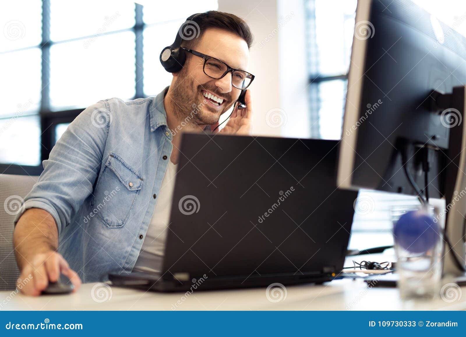 Ung le manlig appellmittoperatör som gör hans jobb med en hörlurar med mikrofon Stående av arbetaren för appellmitt på kontoret