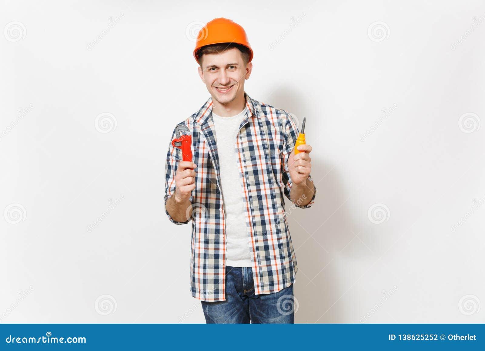 Ung le stilig man i skyddande orange skruvmejsel för hardhatinnehavleksak och justerbara skiftnyckeln som isoleras på vit