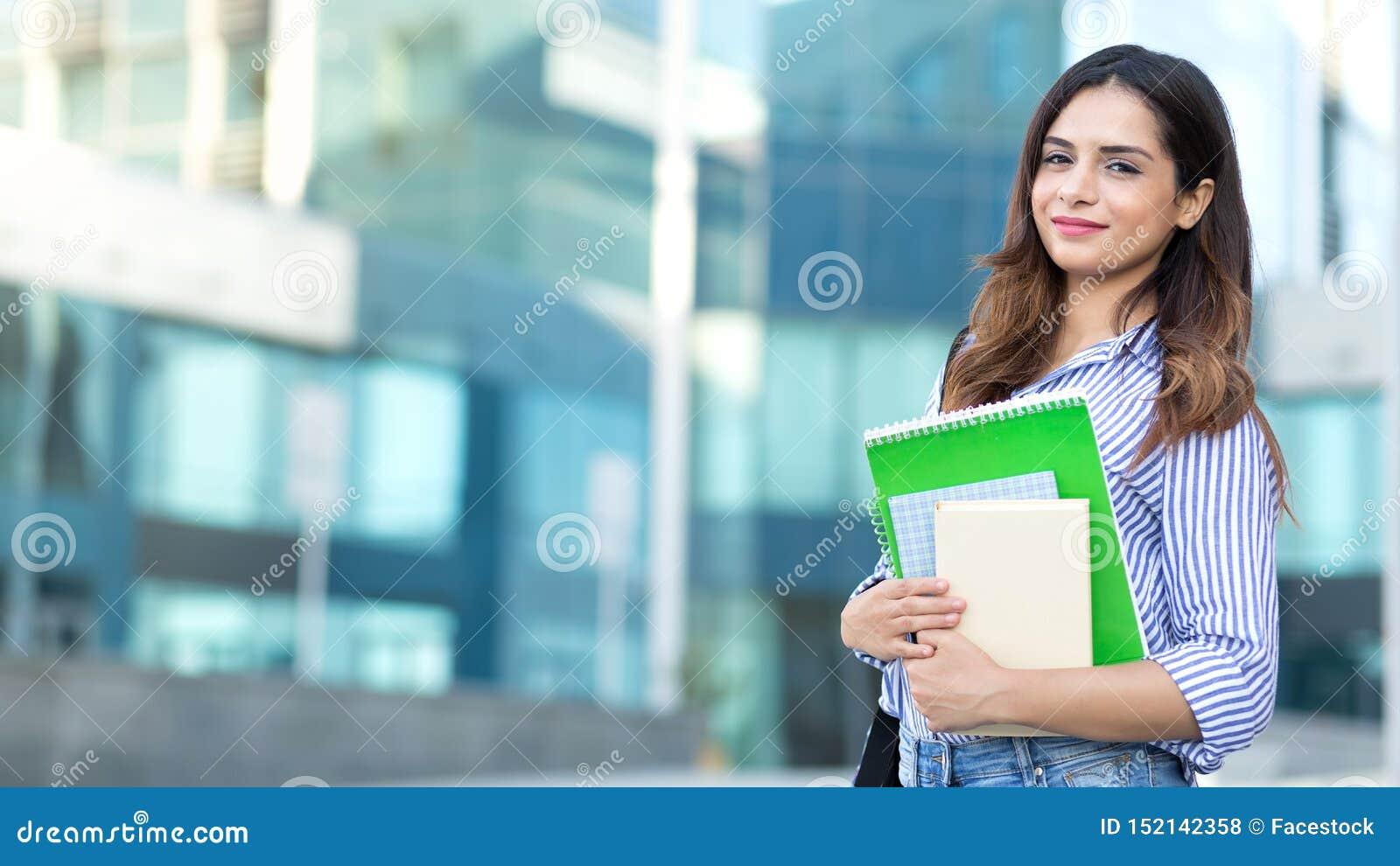 Ung le student som rymmer böcker, studie, utbildning, kunskap, målbegrepp