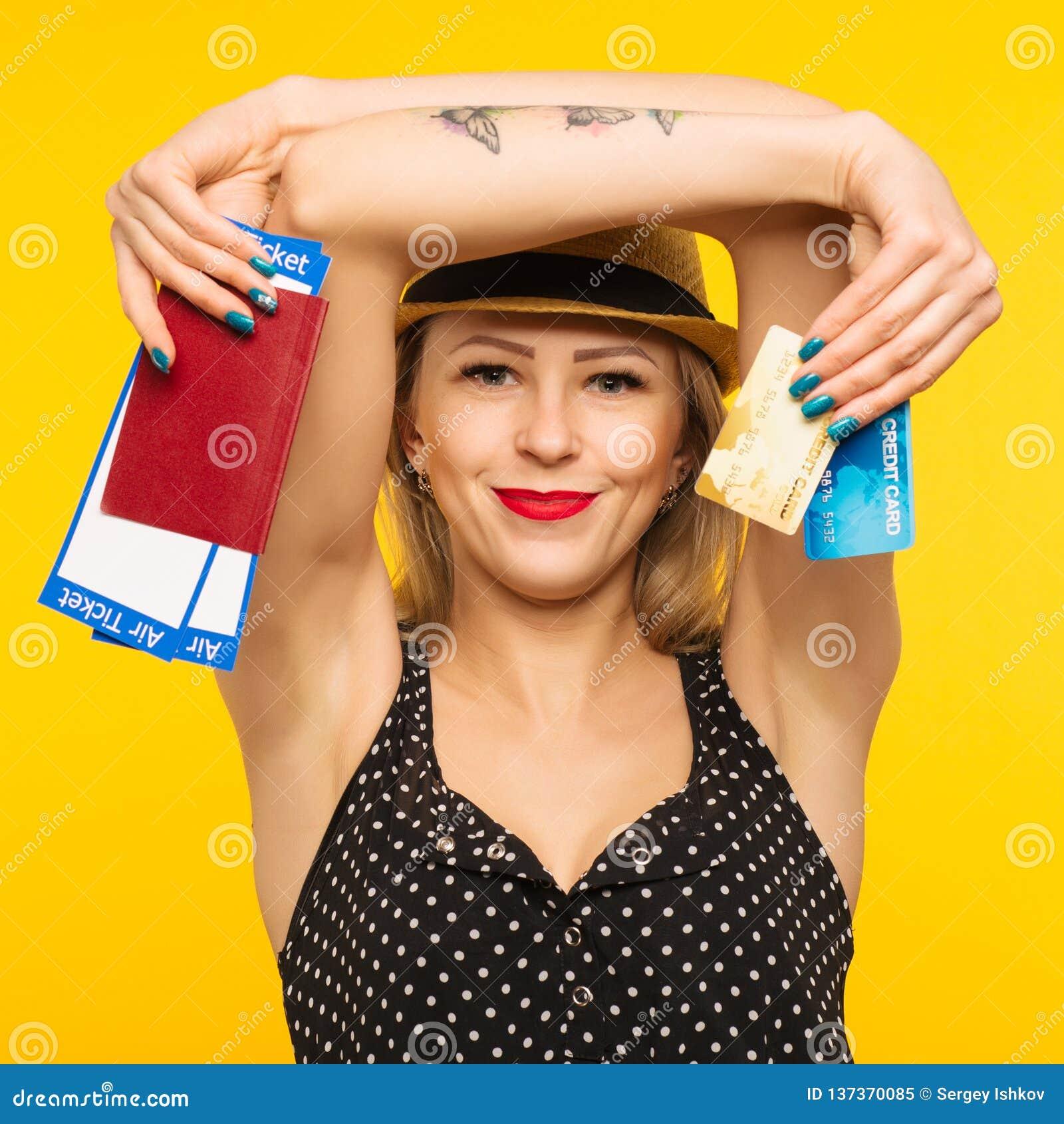 Ung le upphetsad biljett och kreditkort för passerande för logi för pass för innehav för kvinnastudent som isoleras på gul bakgru